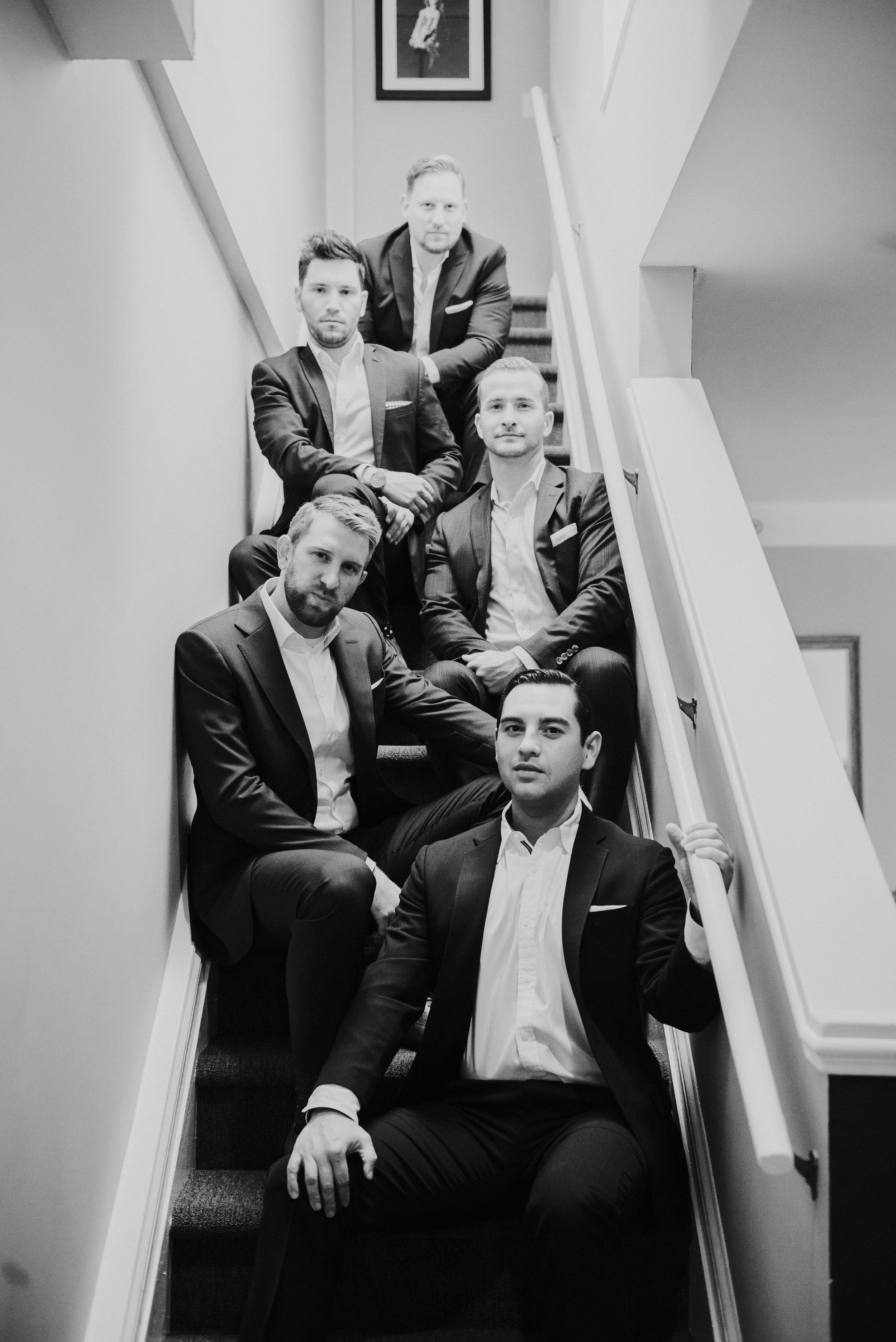 Groom and groomsmen on stairs at Artmore Hotel in Atlanta, GA