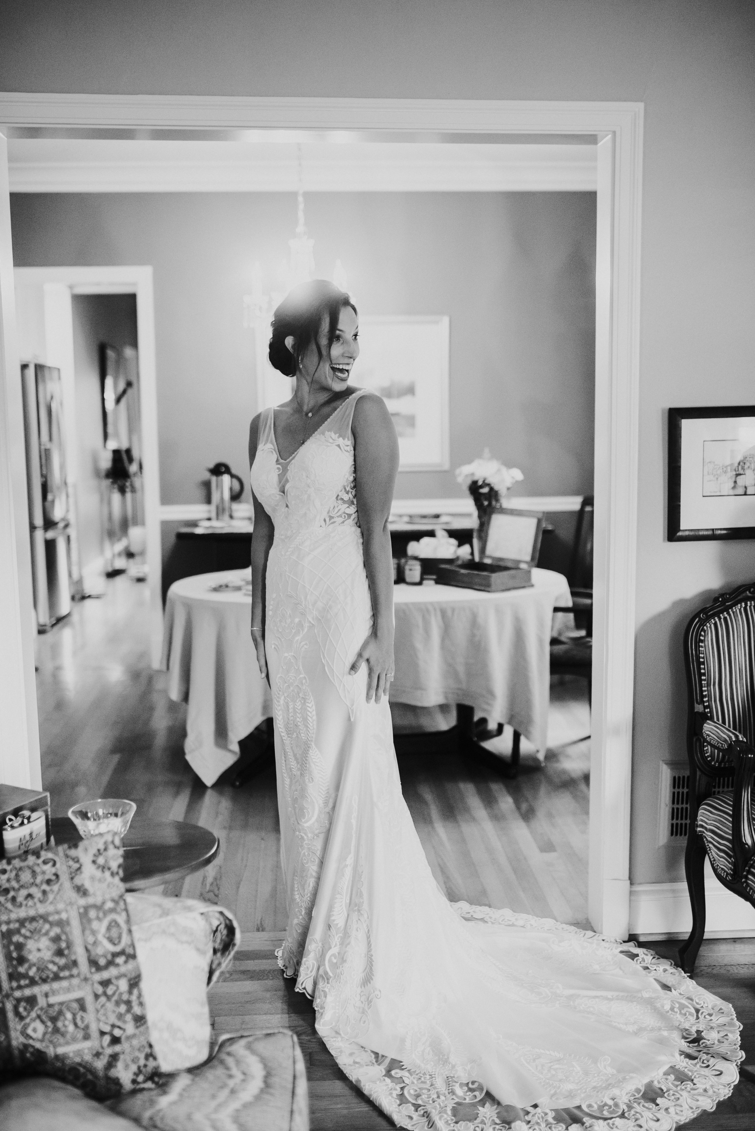 Bride first look with wedding dress in front of bridesmaids