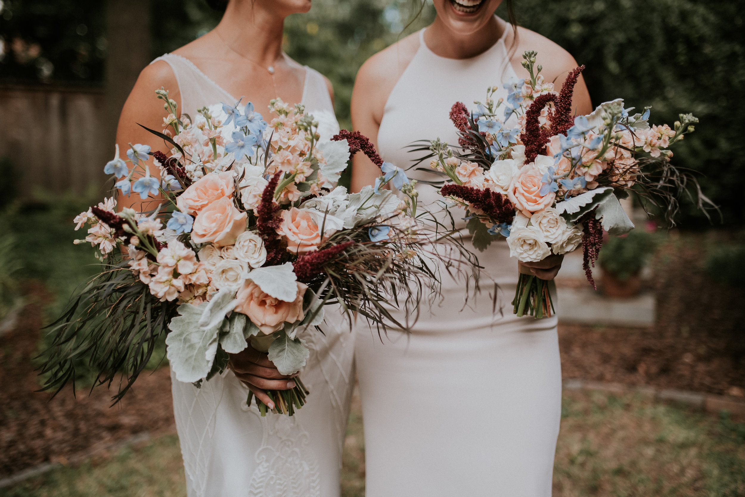 Bride and bridesmaid holding oversized wildflower bouquets
