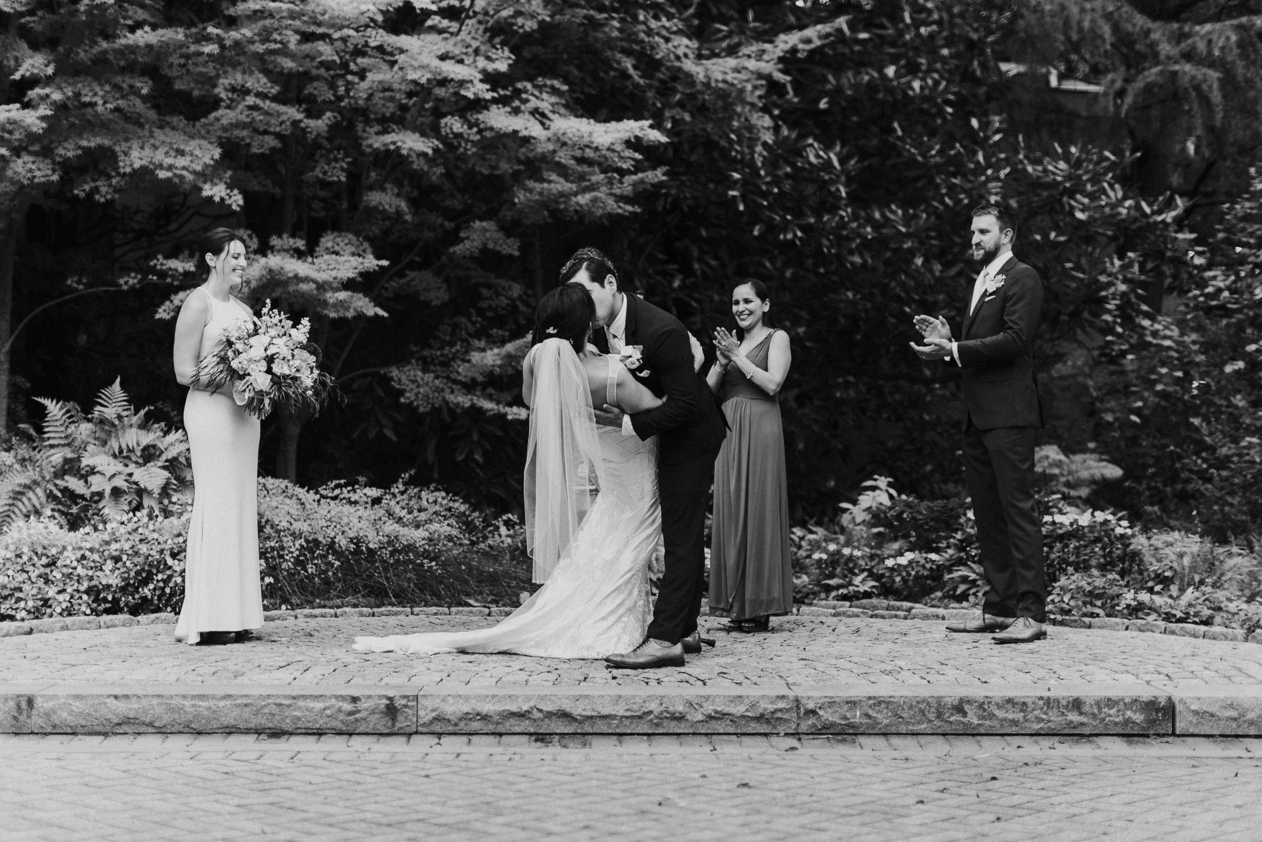 Bride and Groom kiss at wedding ceremony at The Trolley Barn