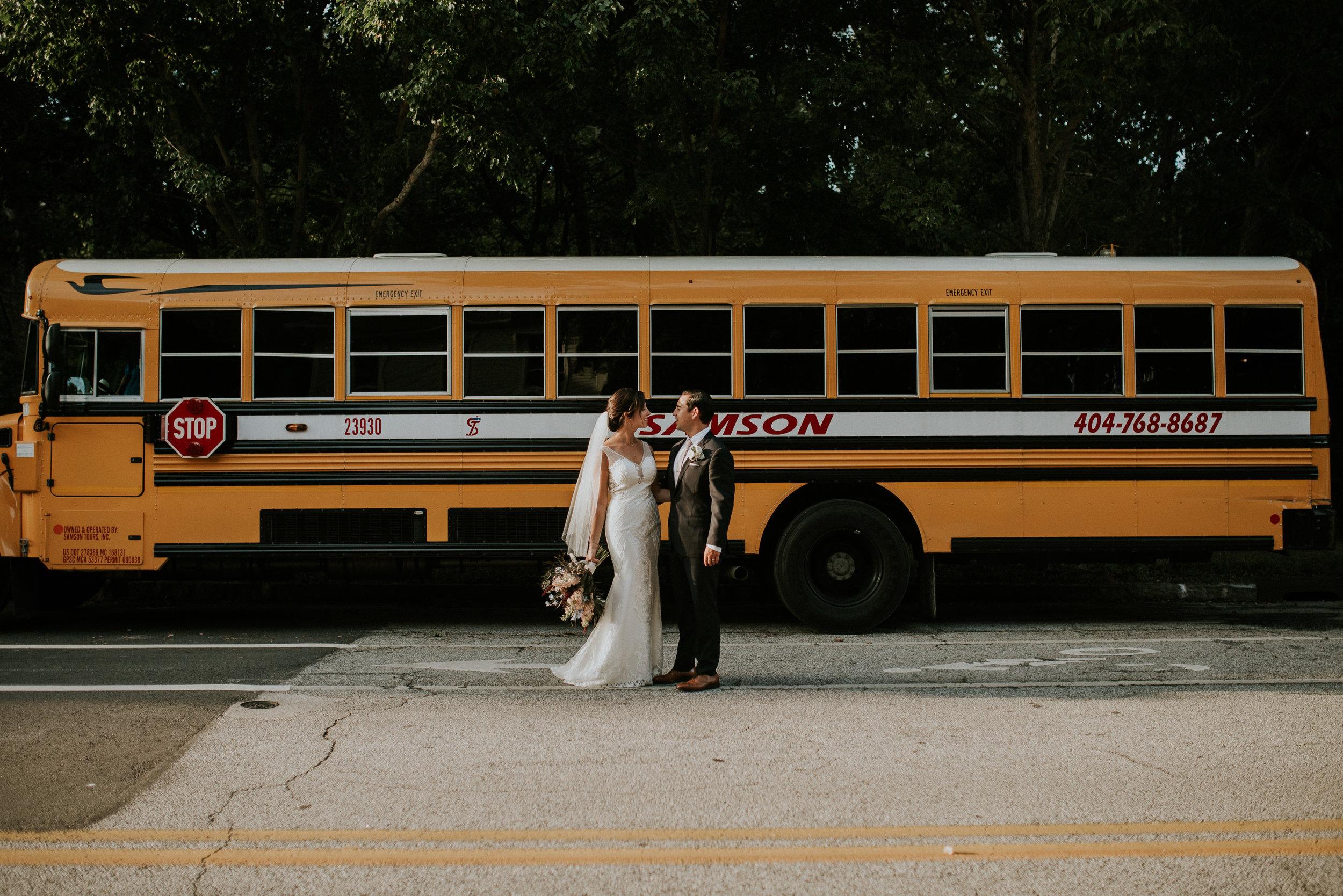 Newlyweds stand near a school bus at The Trolley Barn in Atlanta, GA