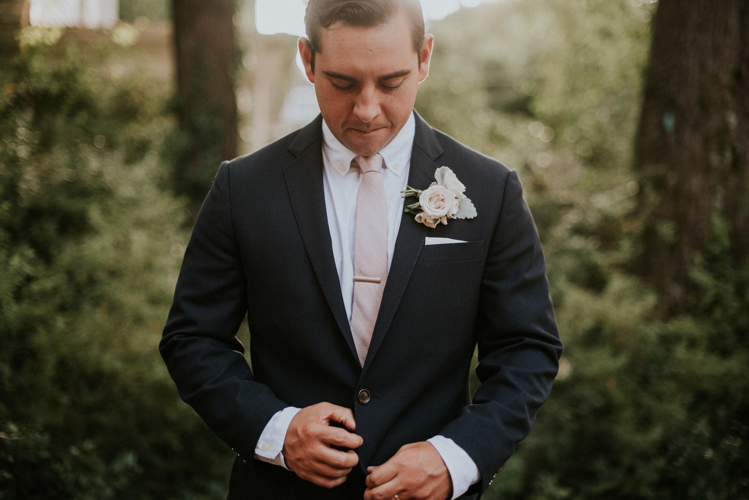 Portrait of groom buttoning navy suit jacket