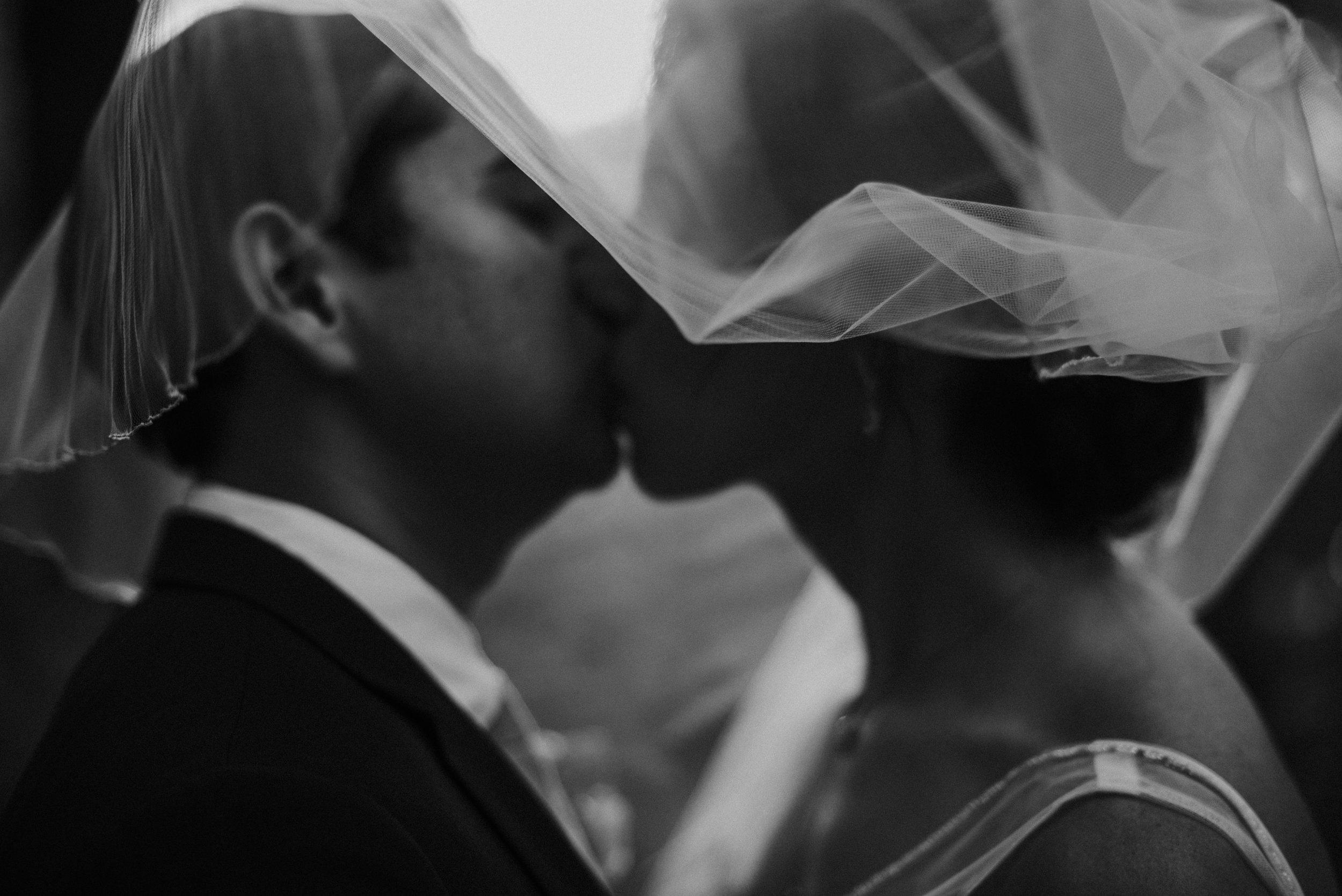 Bride and groom kissing underneath veil