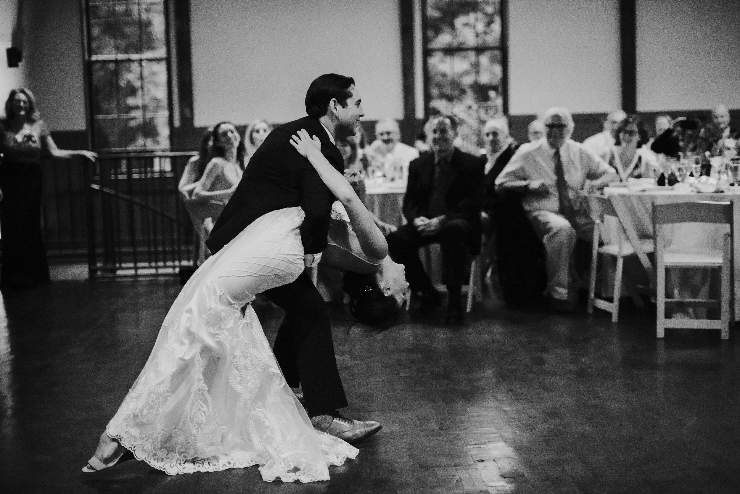 Groom dips bride while dancing