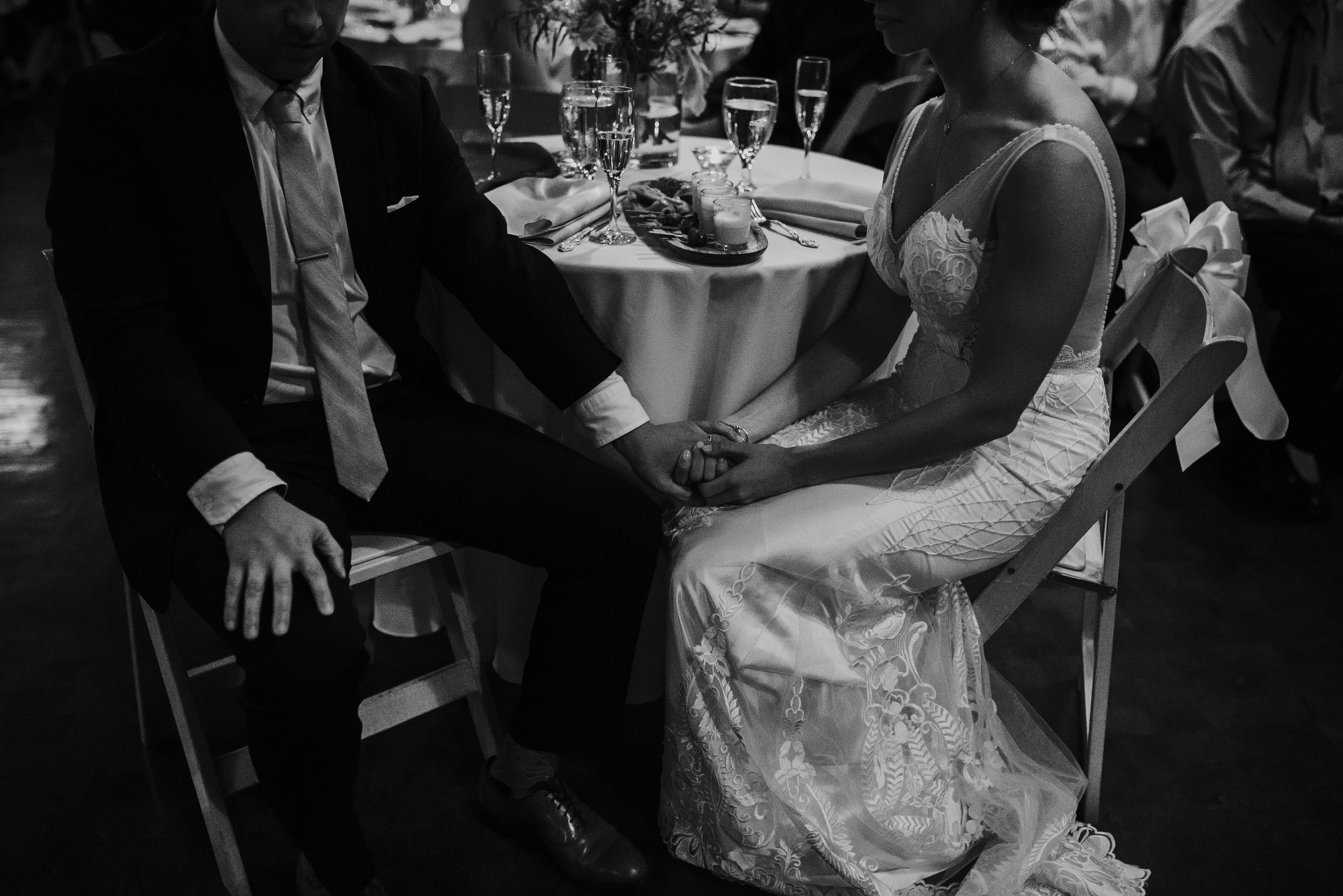 Bride and groom intimately holding hands