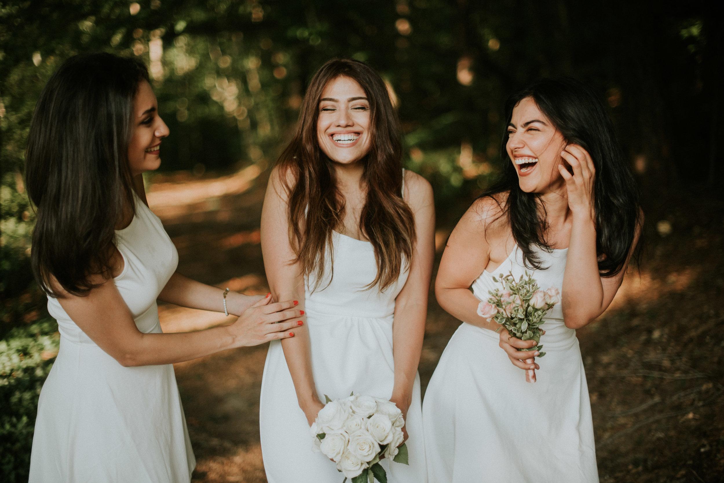 Bride and bridesmaids laughing at elopement