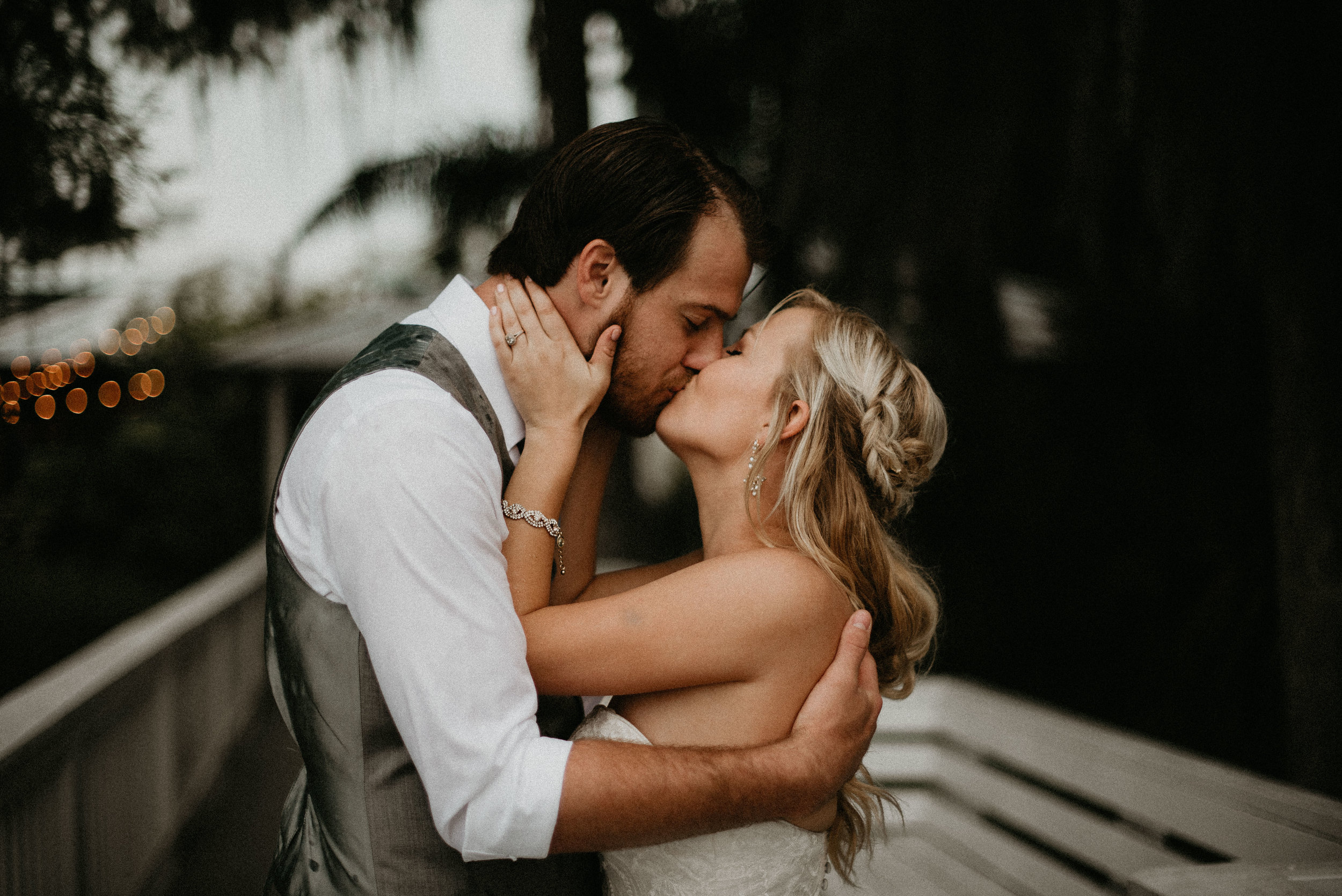 Bride and groom kissing at Paradise Cove dock in Orlando, FL
