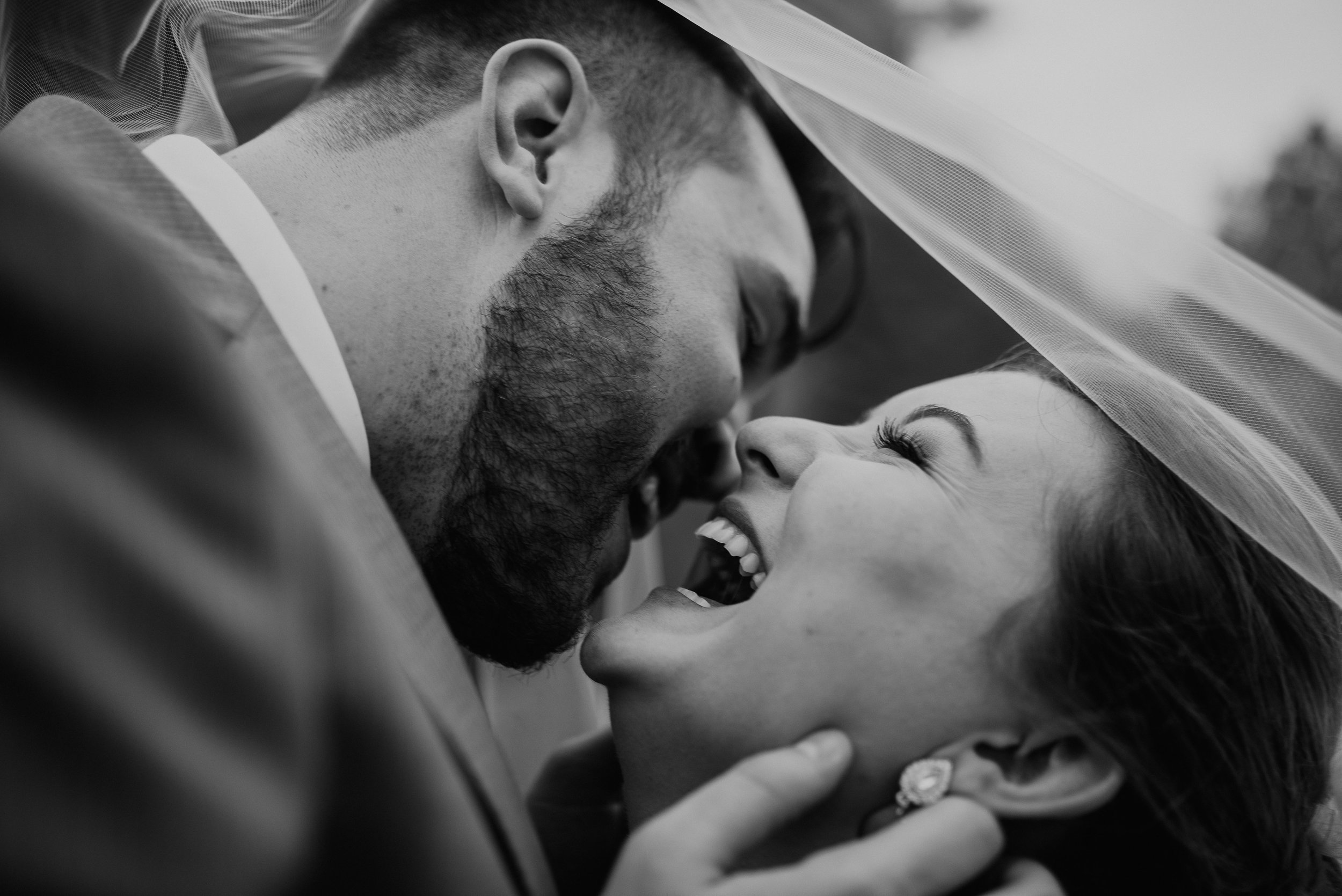 Bride laughing while groom leans in for a kiss