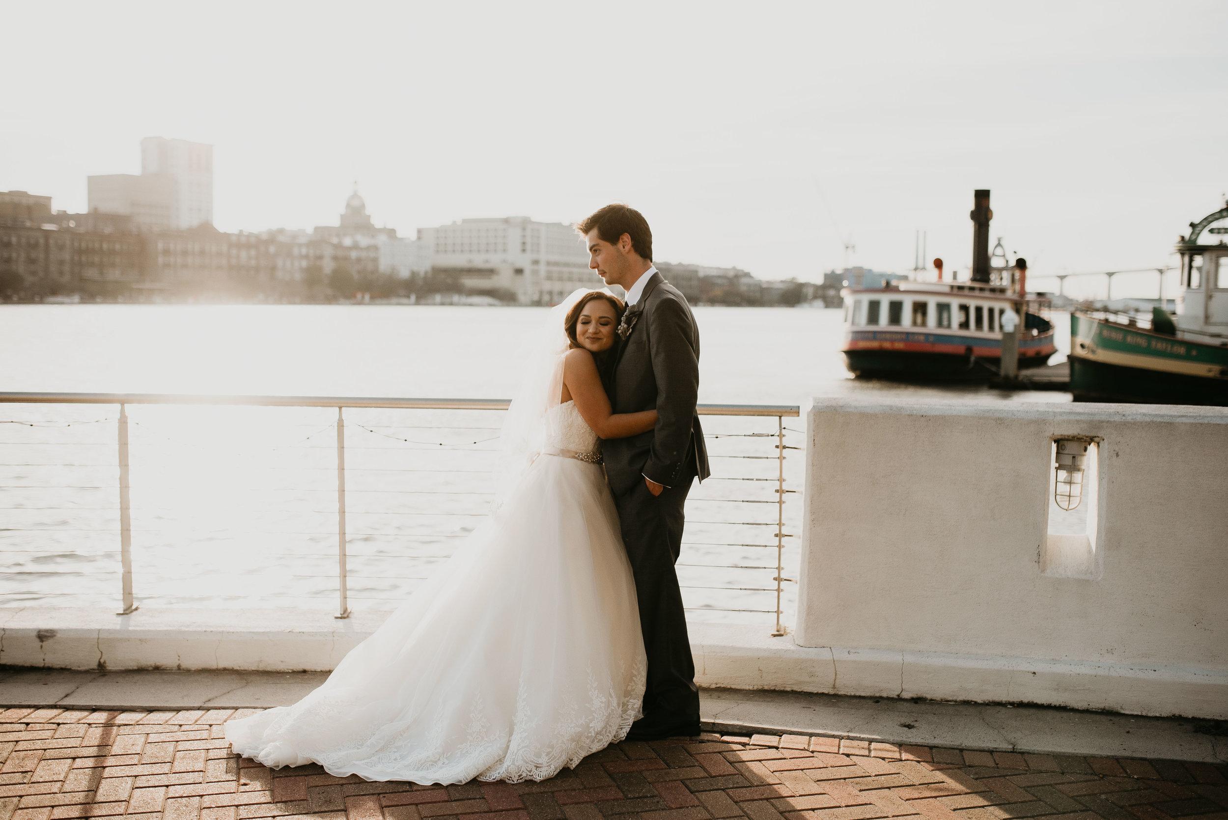 Newlyweds hugging during golden hour at Westin Savannah Harbor in Savannah, GA