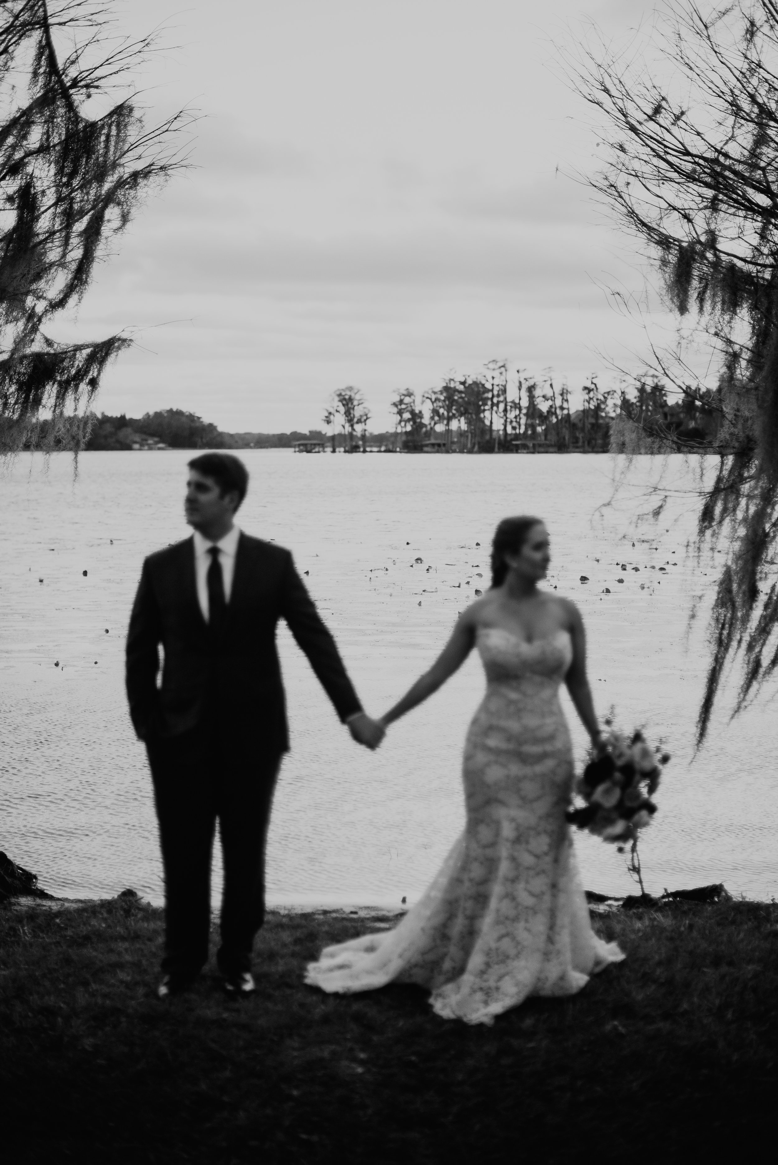 Bride and groom holding hands with lake behind at Cypress Grove Estate House in Orlando, FL