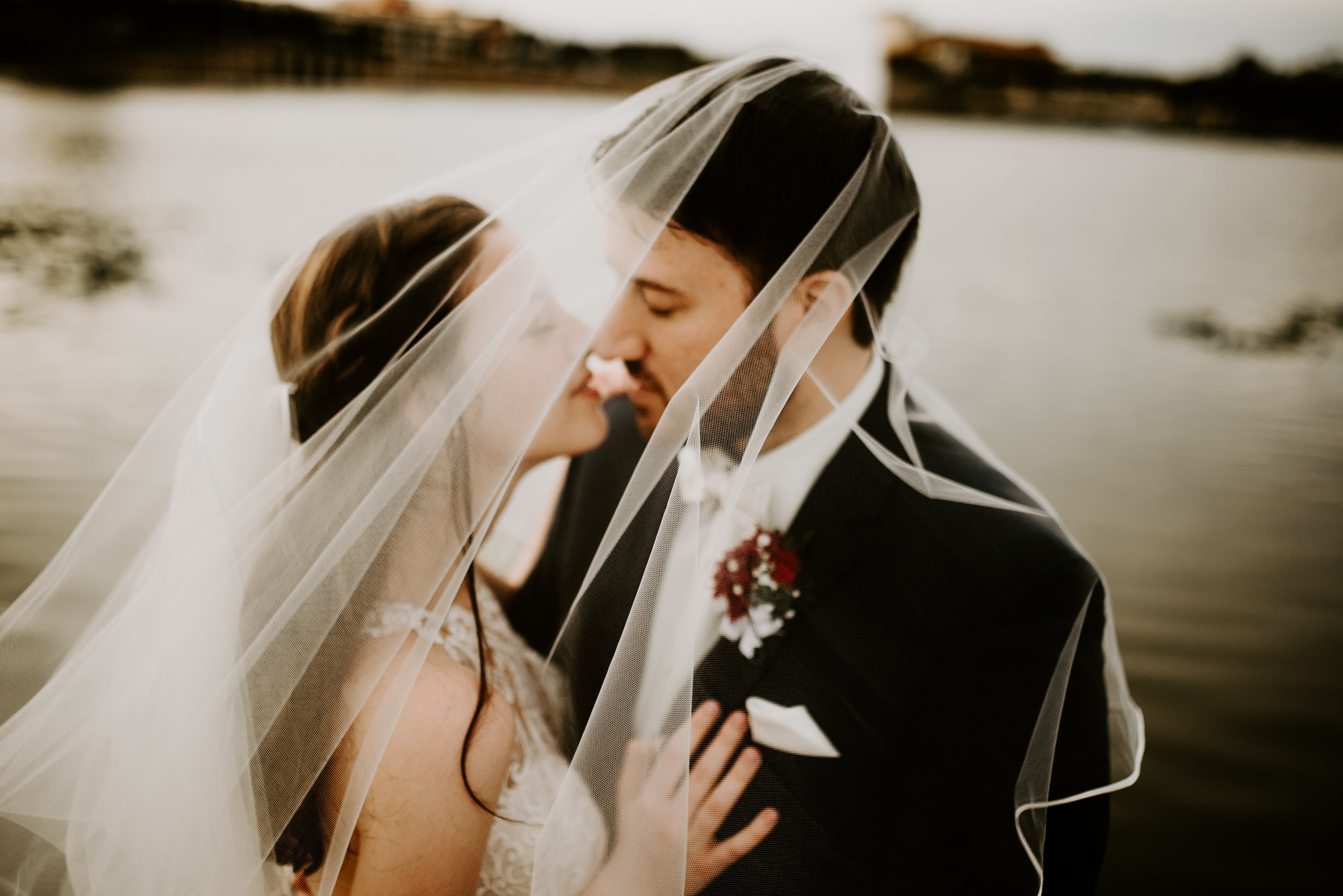 Newlyweds kissing underneath veil with lake in the background