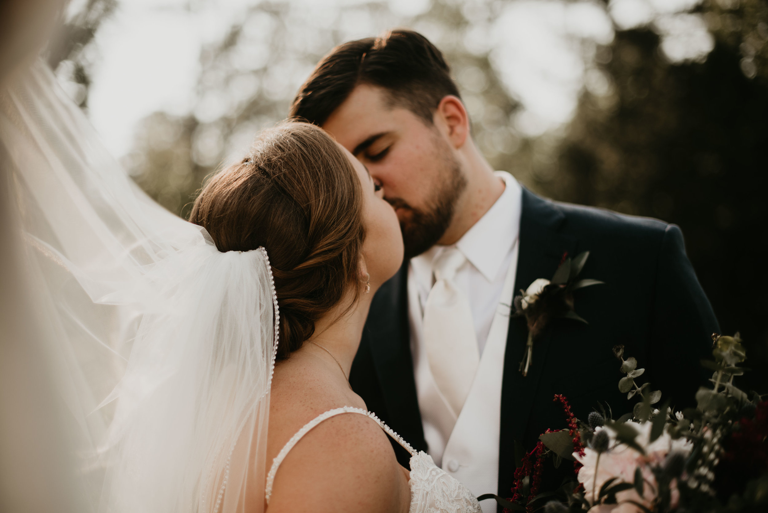 Newlyweds kissing with wind-blown veil