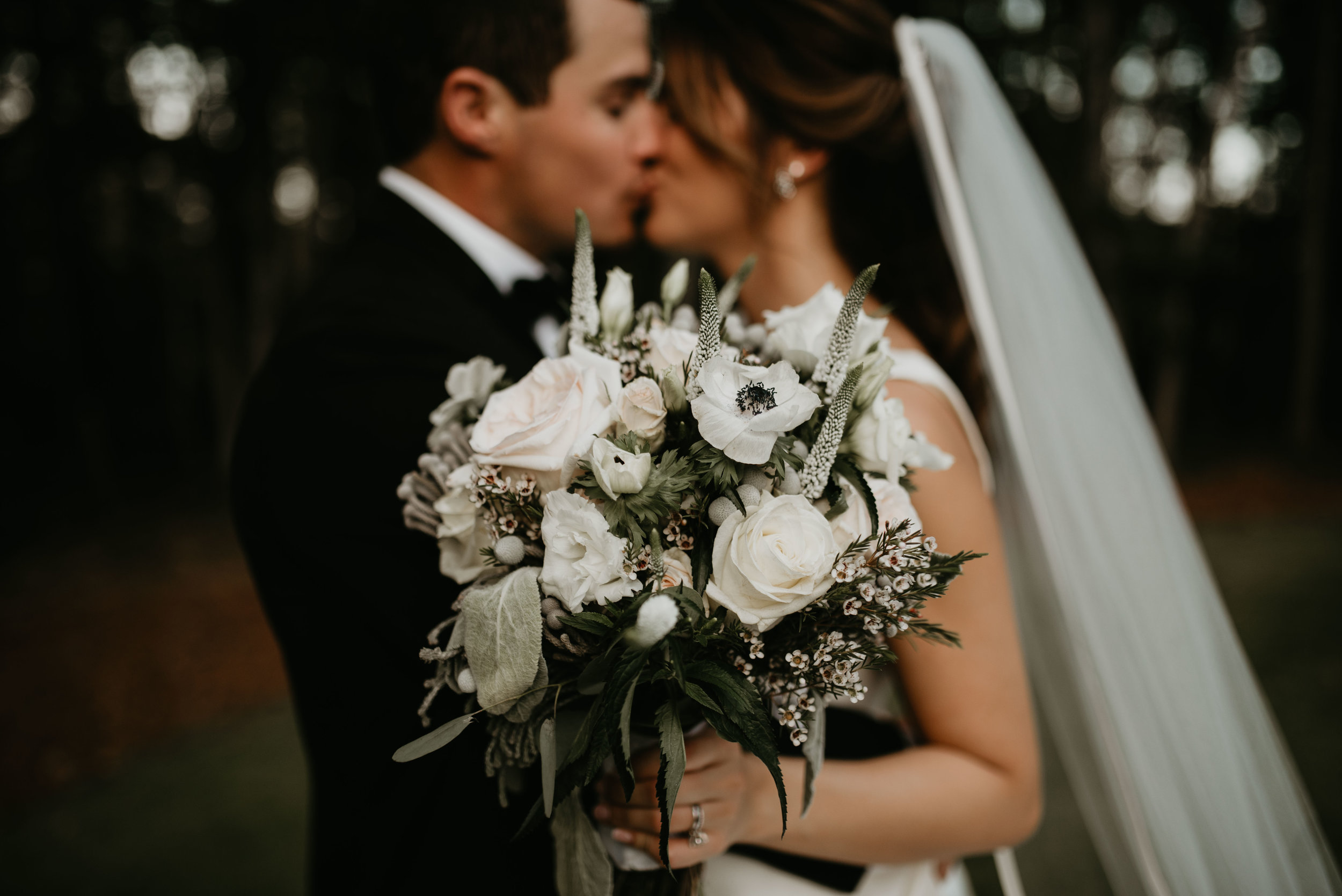 Bridal bouquet with bride and groom kissing in background