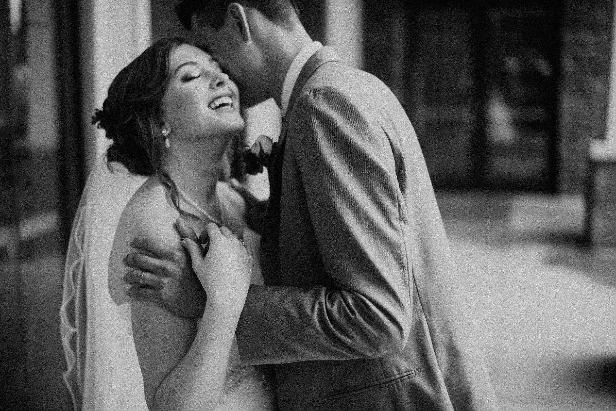 Groom whispering into bride's ear