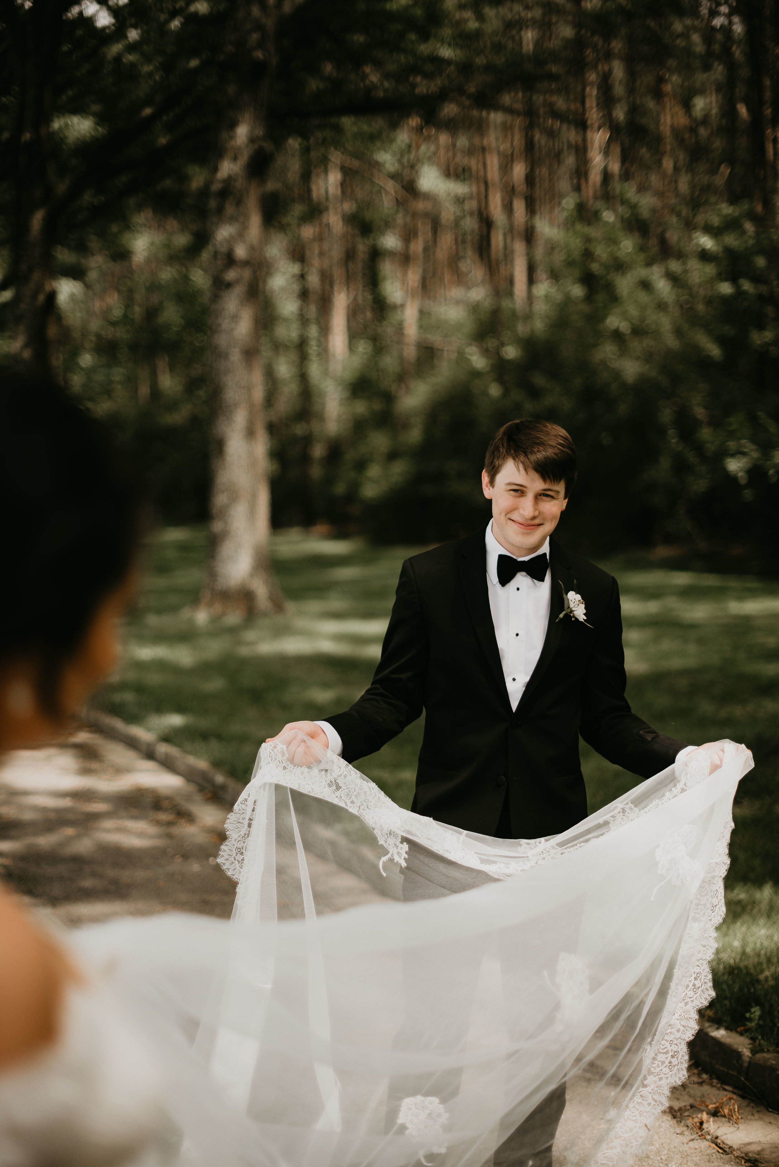 Groom holding bride's wedding dress and smiling at Berry College wedding