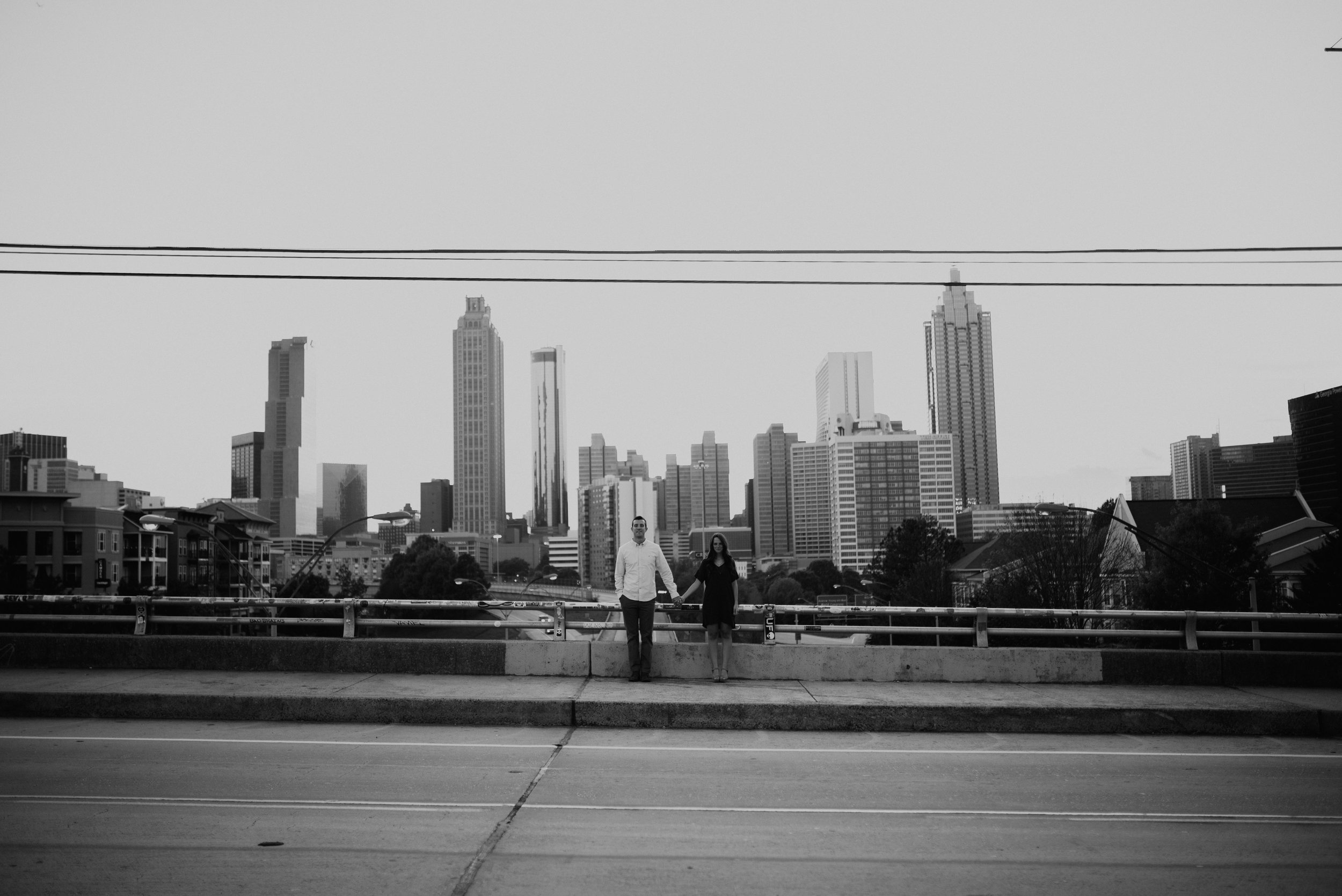 couple holding hands with atlanta skyline behind them jackson street bridge