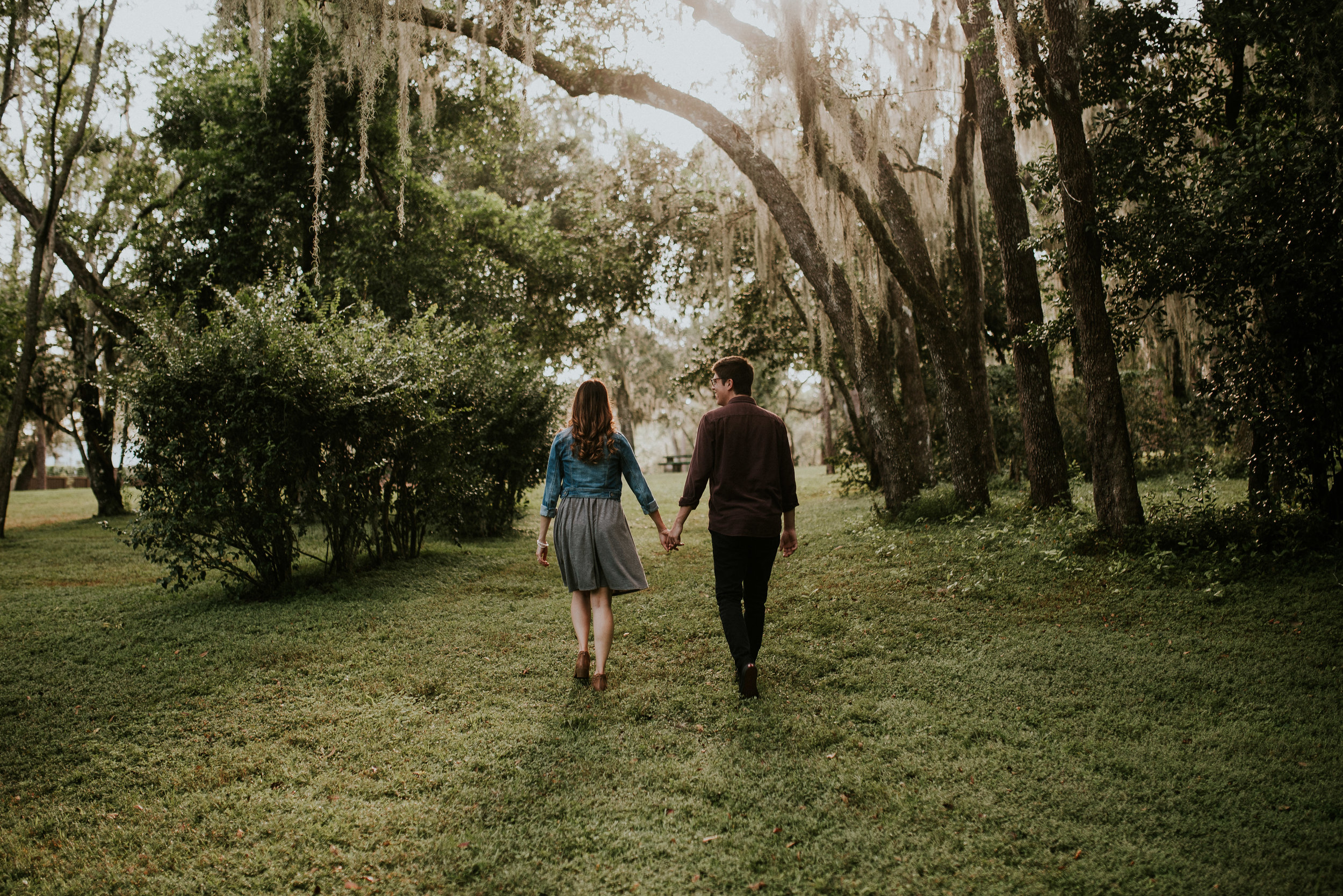 couple holding hands and walking away at mead botanical garden engagement