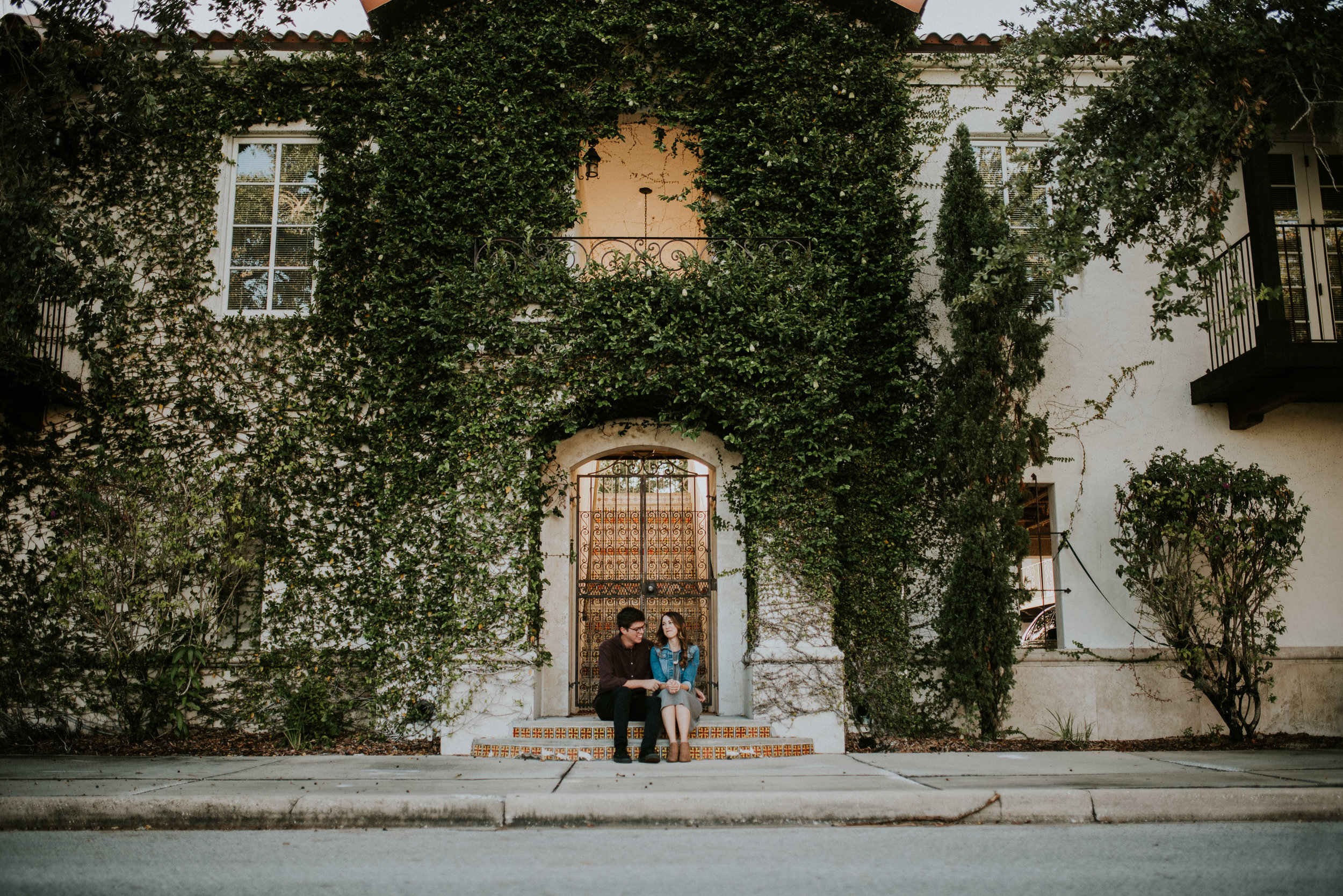 couple sits beside eachother by wall with ivy winter park engagement