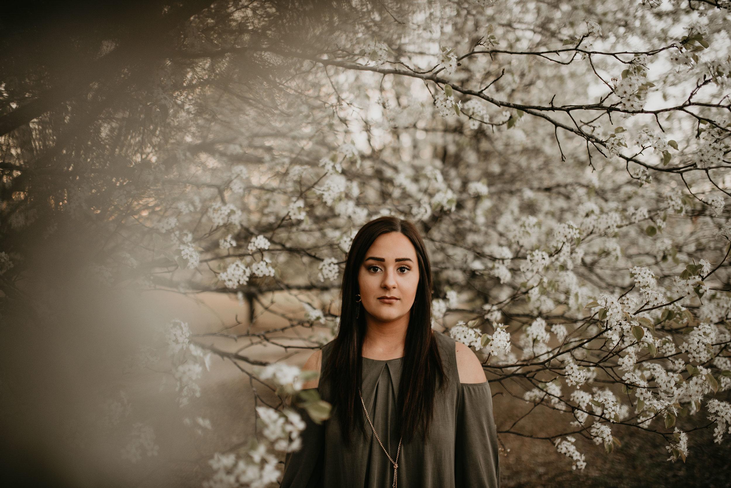 senior girl poses in white spring blooms for session in atlanta