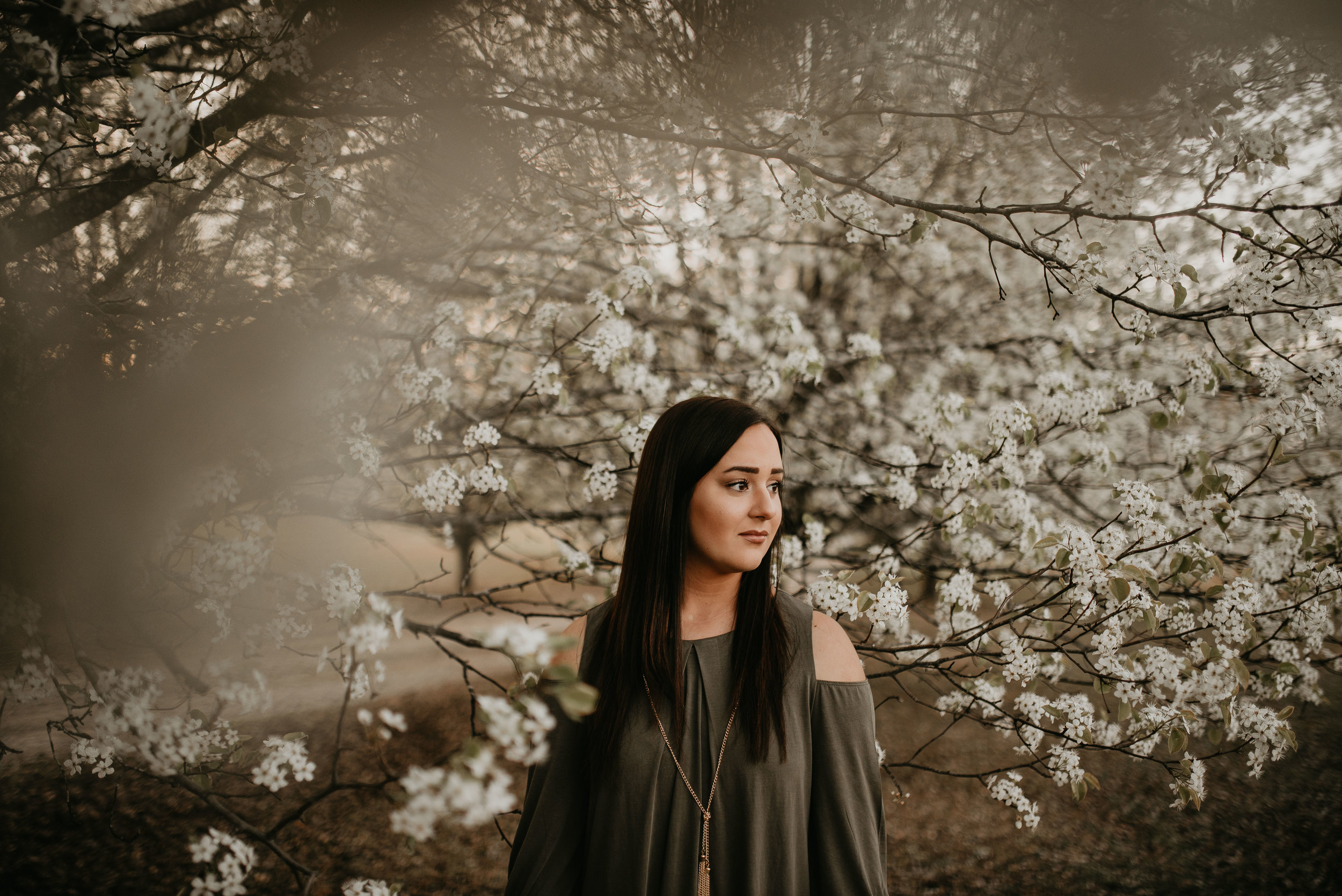 graduating senior girl poses in white spring blooms for atlanta senior session