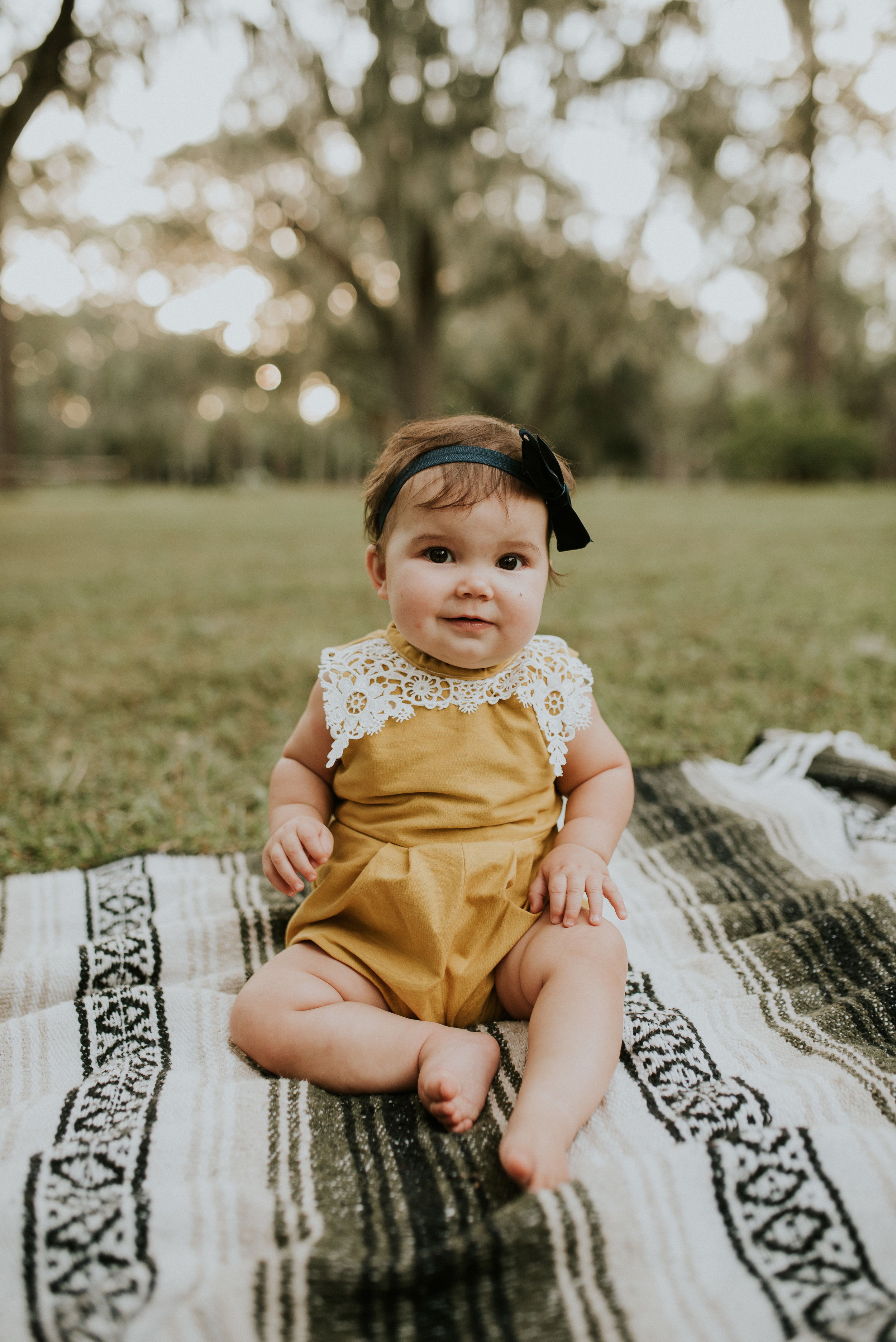 baby girl sitting on blanket family photos at mead botanical garden orlando