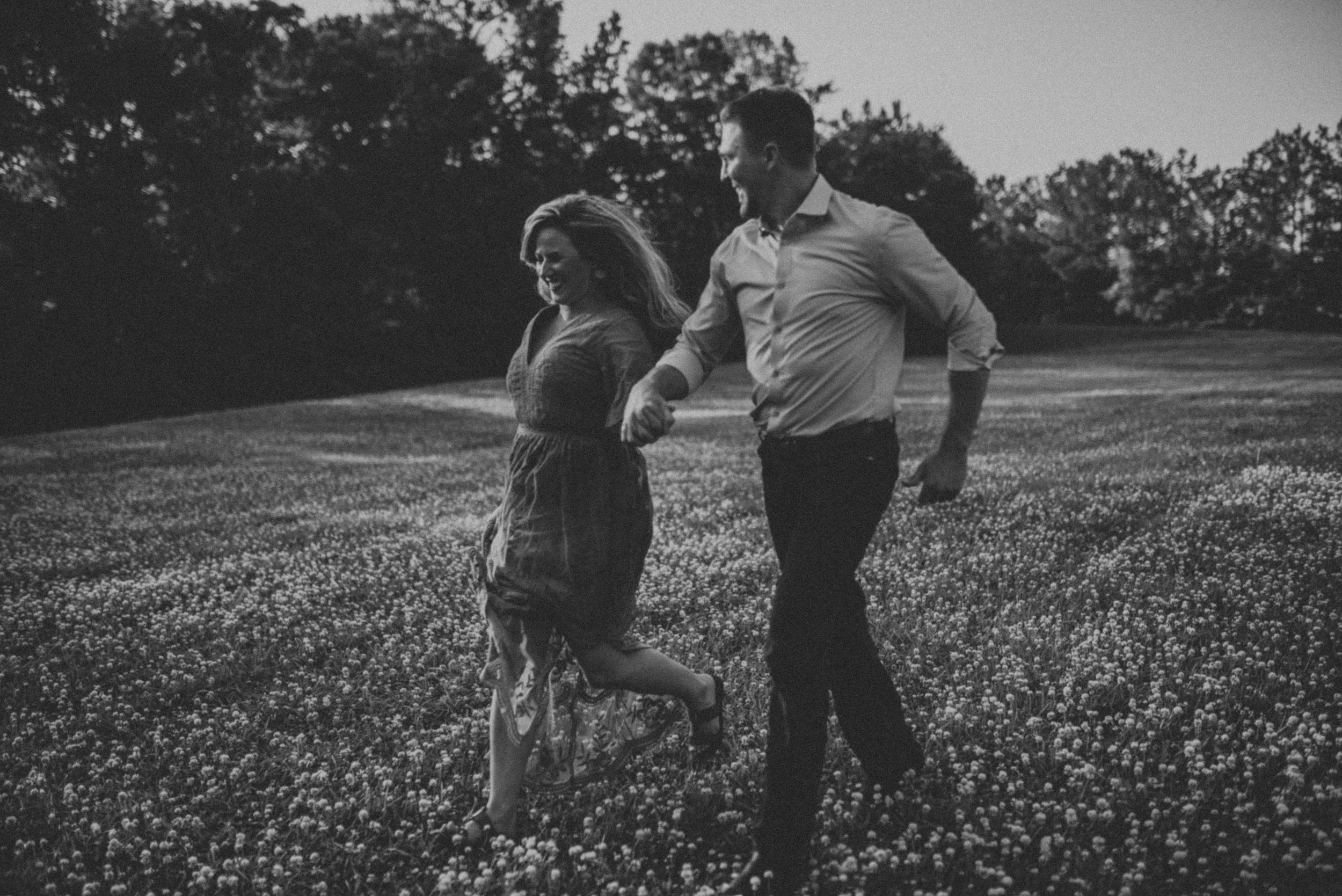couple running through flowers in sweet meadow farms engagement session