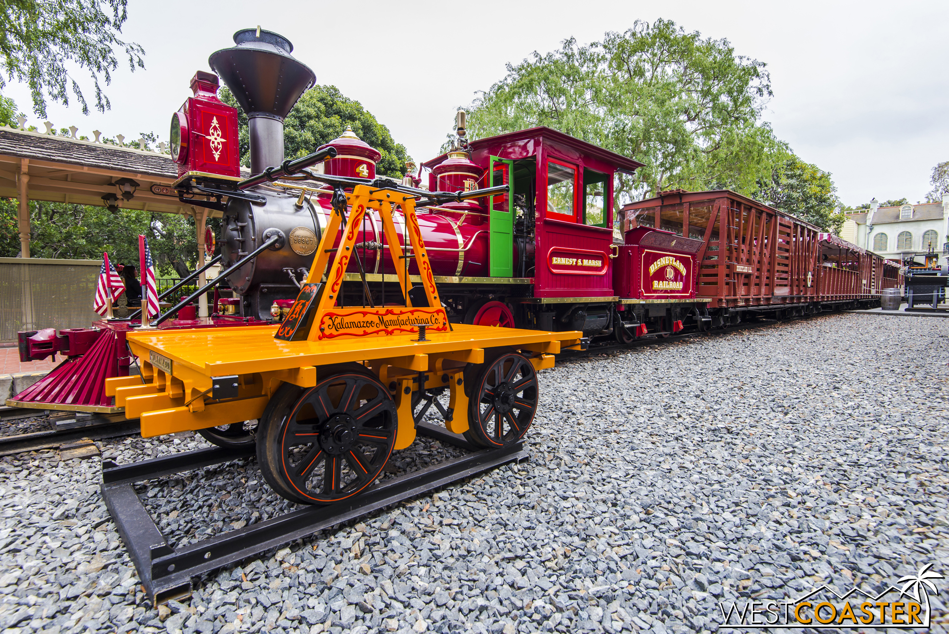 A handcar stands beside the train.