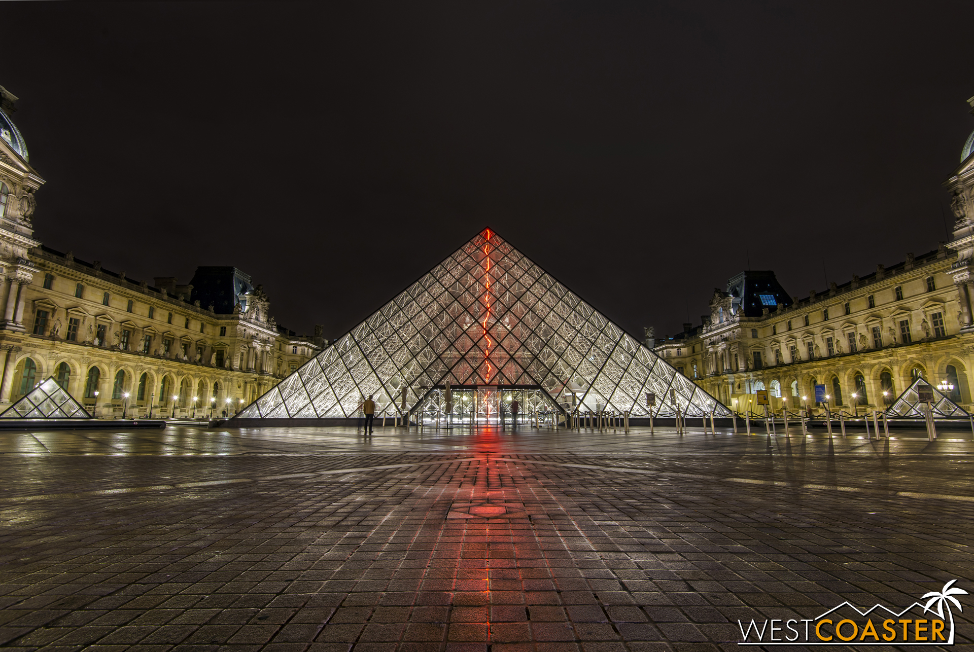 The I.M. Pei-designed glass pyramid of the Louvre, illuminated late at night.