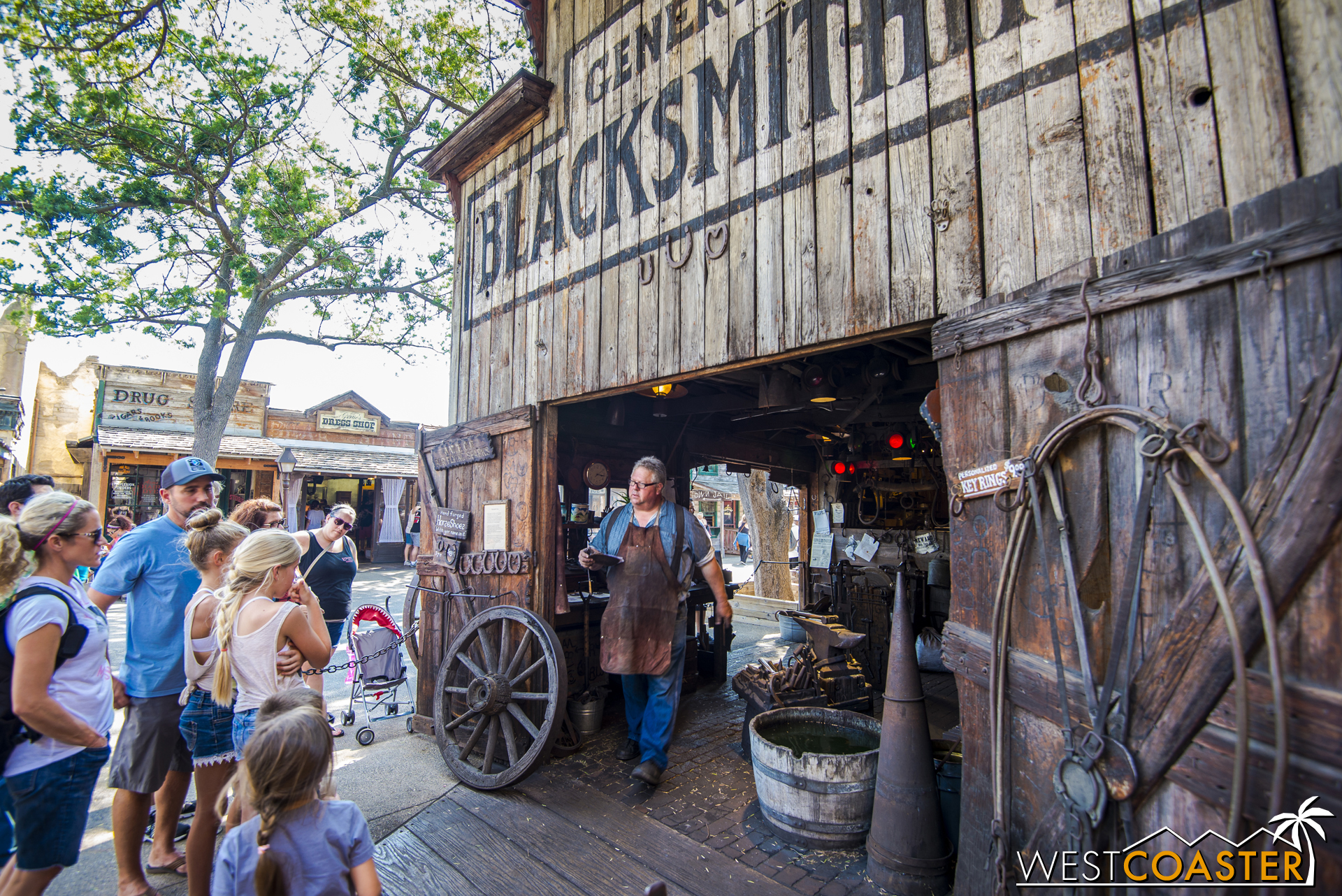 A crowd gathers around to see the town blacksmith at work.