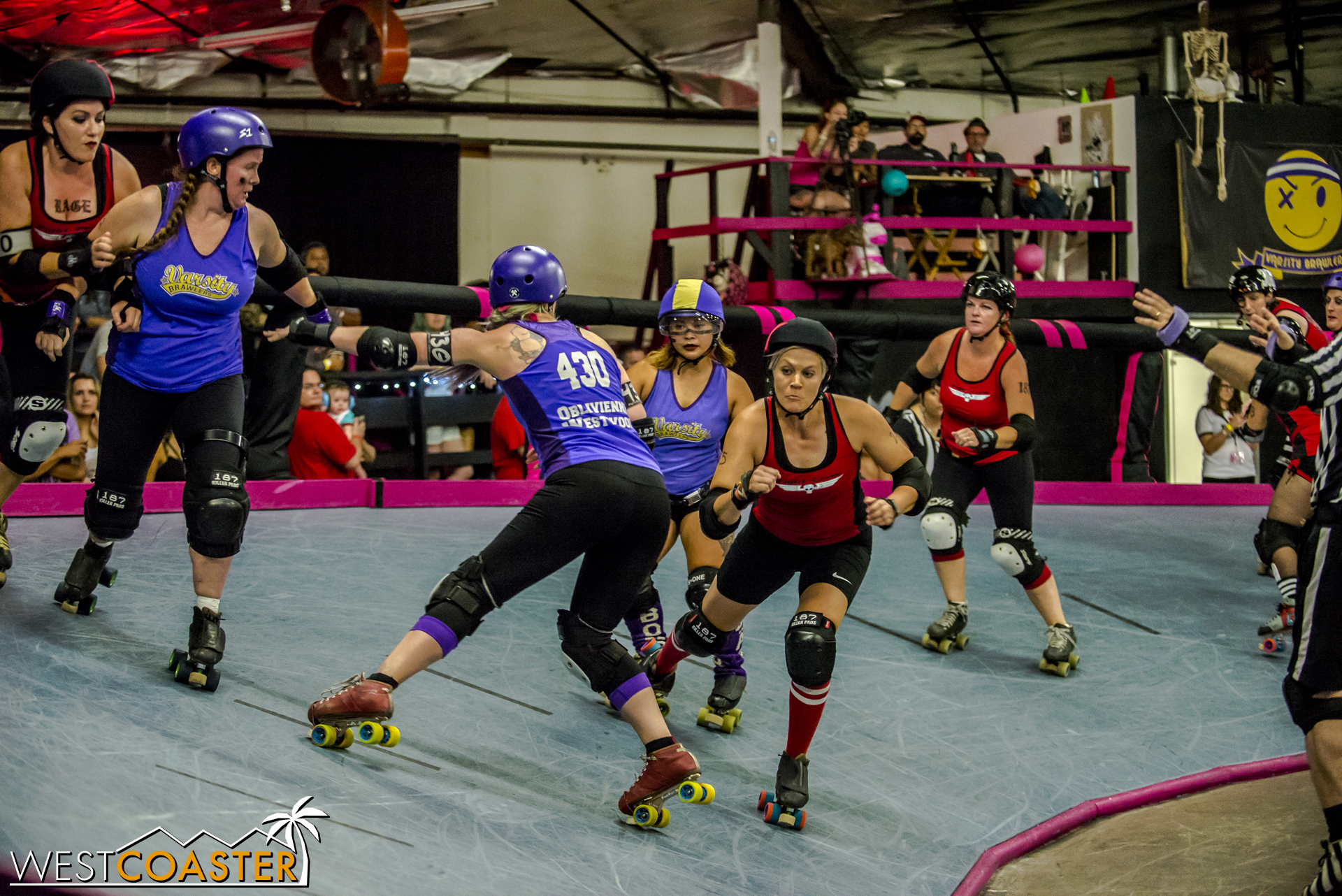 As a blocker attempts to hip check, the red-clad Fight Crew jammer shifts to evade the check.