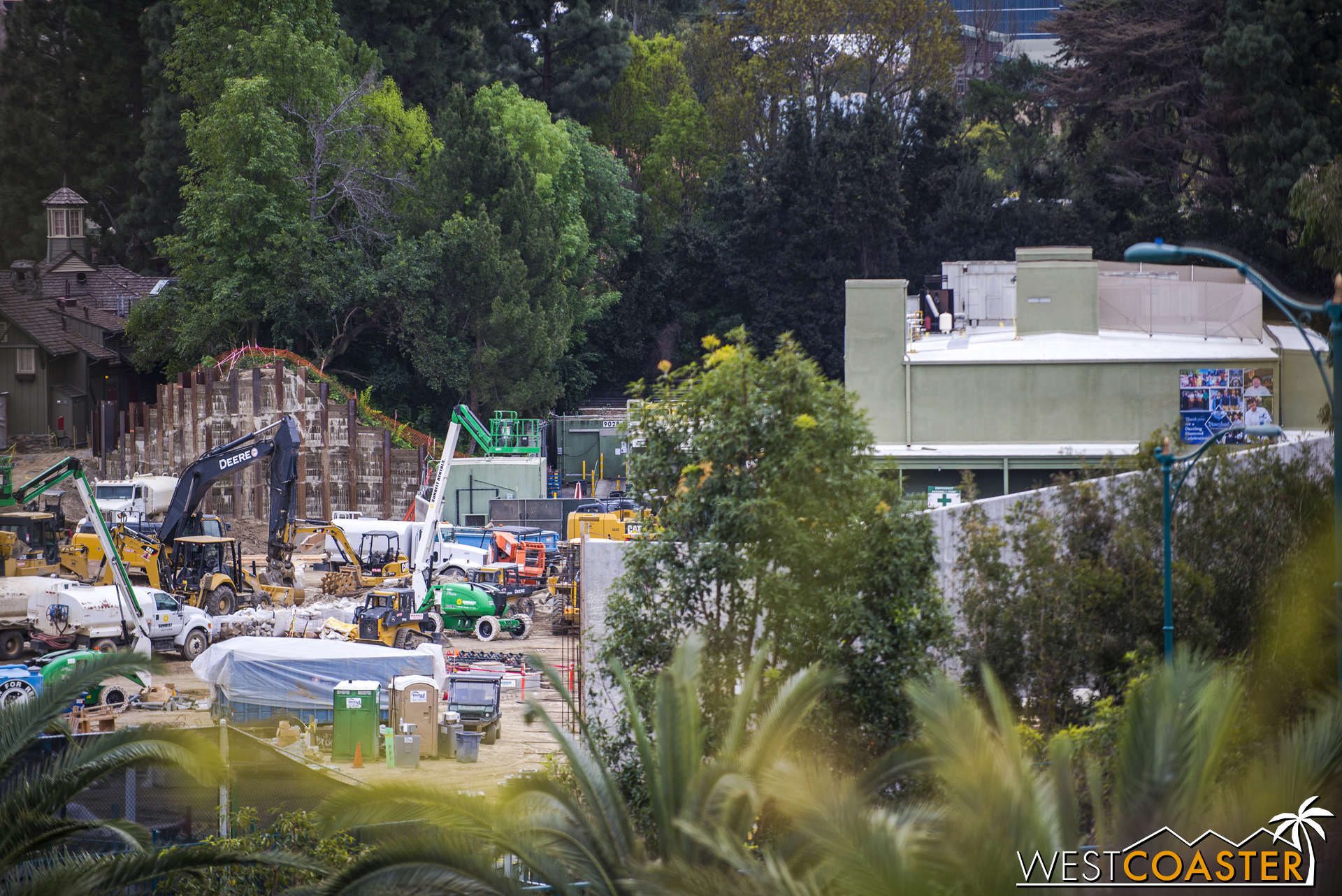 Because, remember, the Disneyland Railroad is still crossing over the Critter Country pathway between The Many Adventures of Winnie the Pooh (green building on the right) and the Hungry Bear Restaurant. So about left of the berm retaining wall in this photo. But then (if we're to trust the rendering Disney previously released), it runs visibly along the reconfigured bank of the Rivers of America.