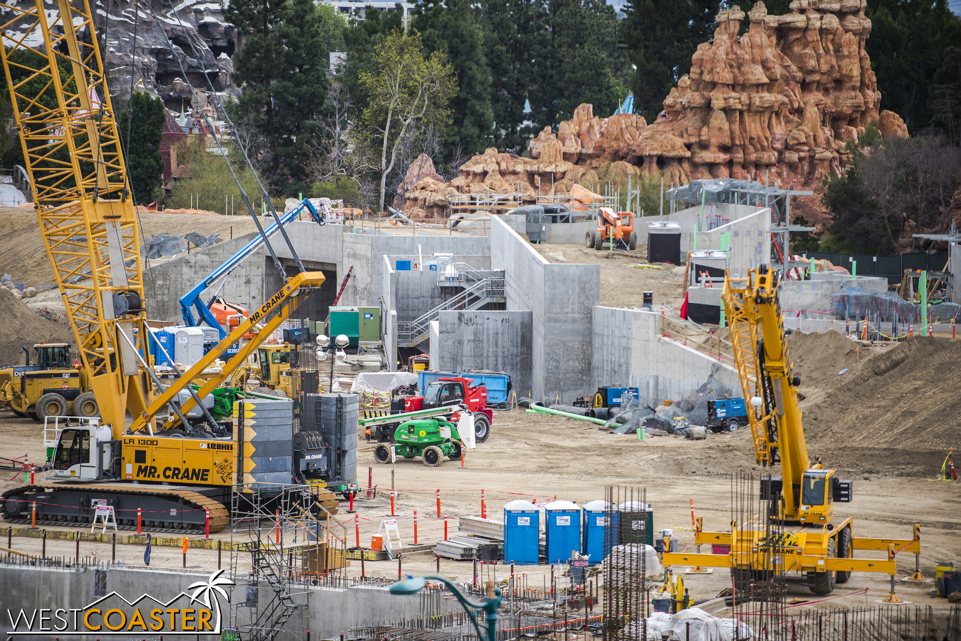 """Some stairs have sprung up along the concrete retaining walls supporting the berm and service drive over the future """"Star Wars"""" Land main entrance section."""