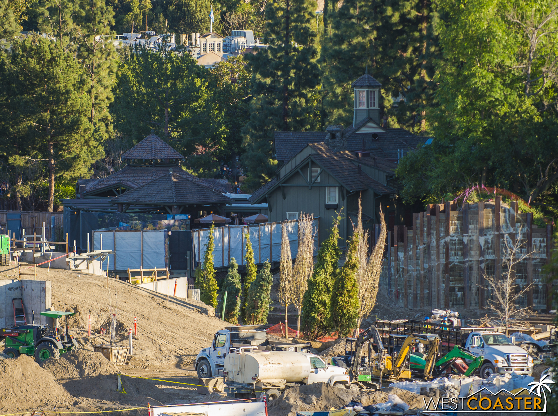 When it reopens, the Disneyland Railroad will still be reappearing just to the right of the Hungry Bear Restaurant building and left of the berm on the right that has been cut and shored up.