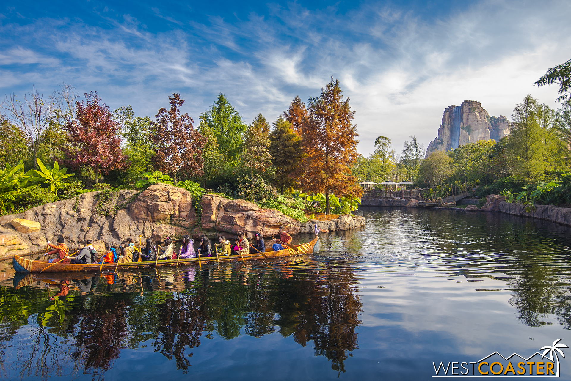Canoe paddlers row through a waterway, past Roaring Mountain in the distance.