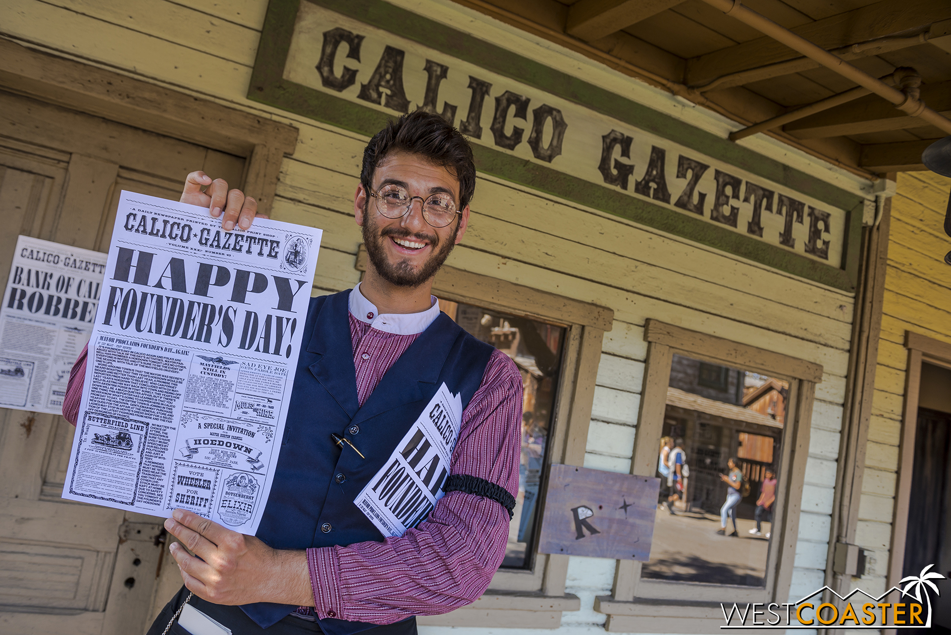 Newspaper editor Bixby Knolls holds up the latest edition of the Calico Gazette, which makes multiple printings a day and even includes the names of some interacting guests.