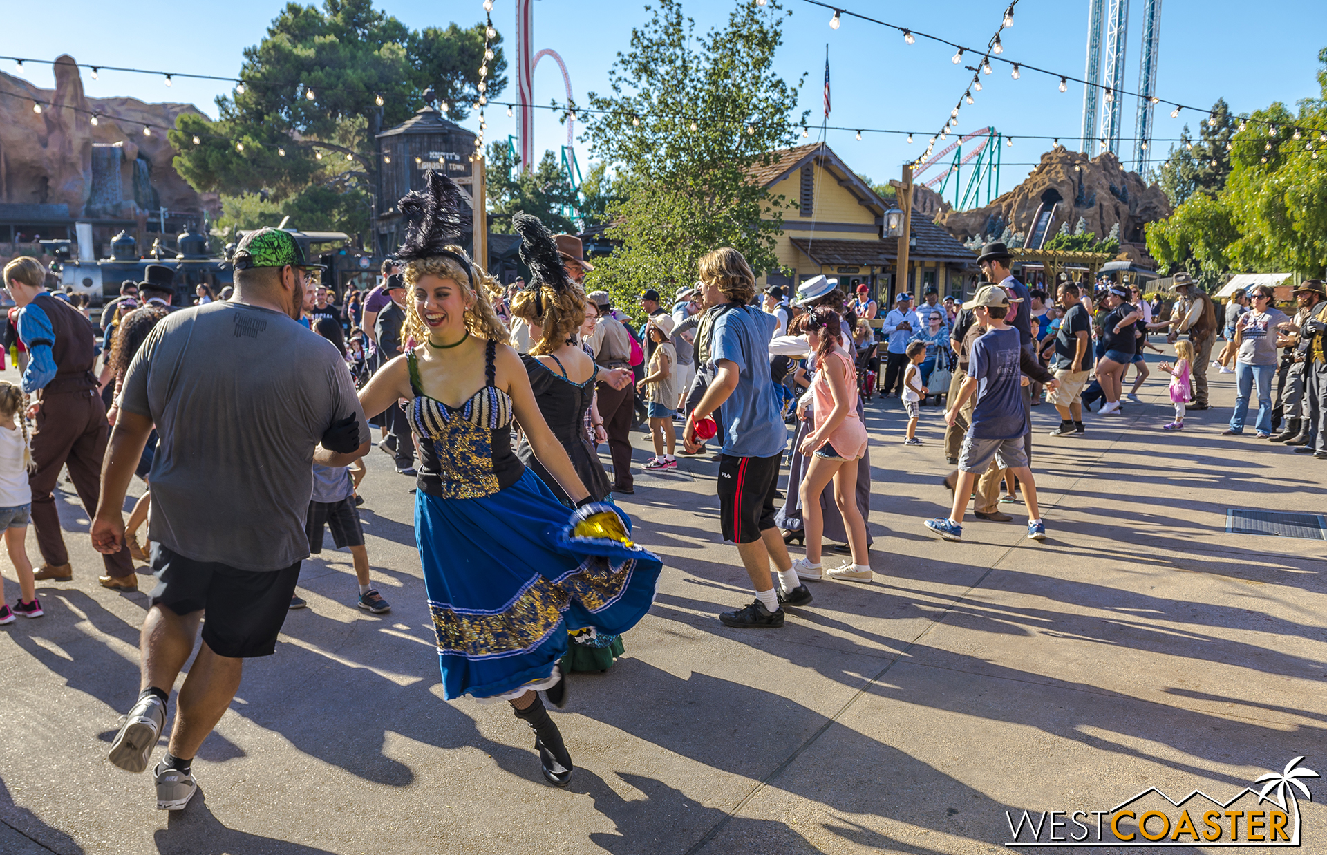 The crowd engages in several line and country dances, taught to them by the Citizens.