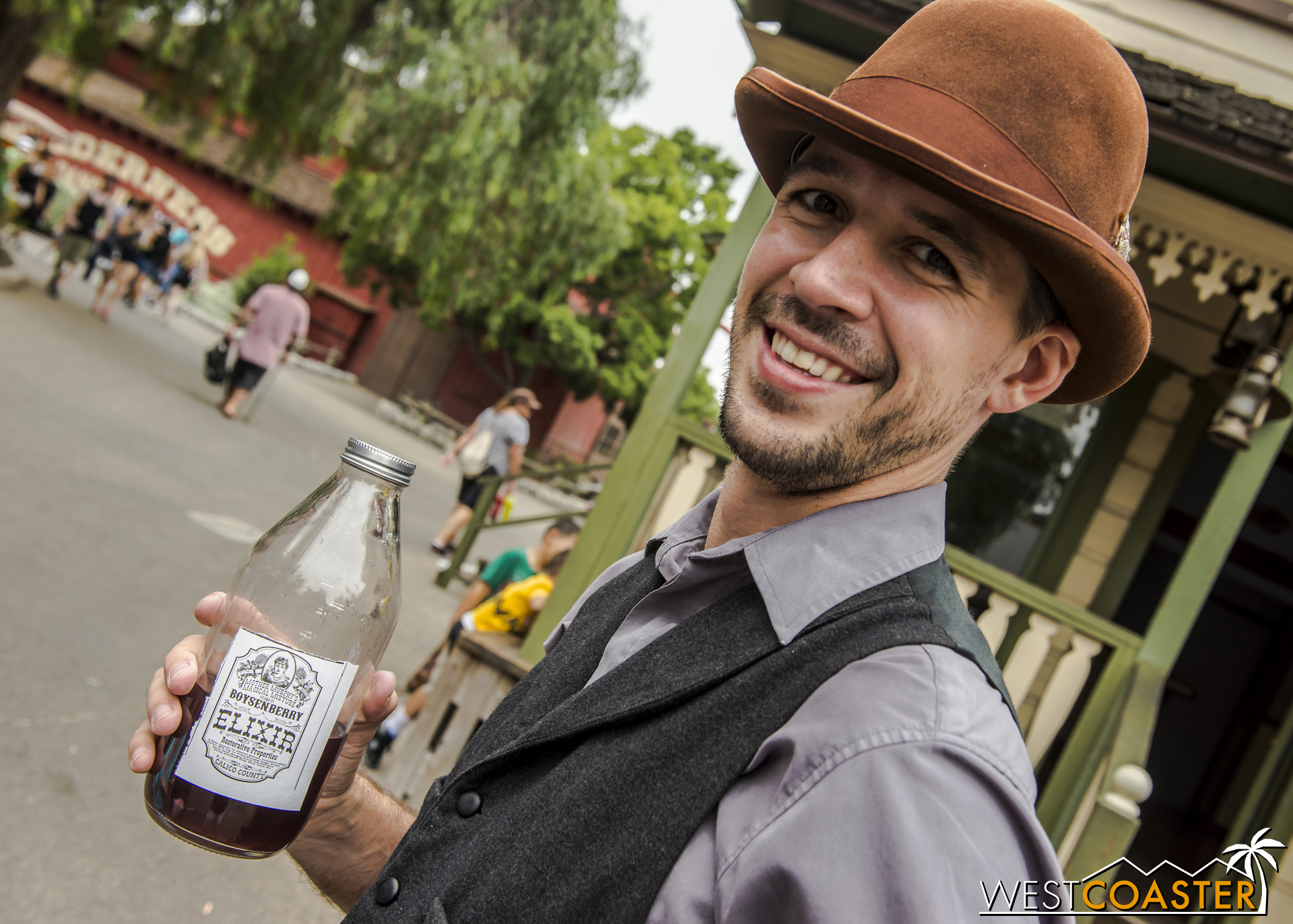 Town Clerk, Kenny Storm, enjoys a swig of Mother Murphy's Magical Boysenberry Elixir in a bottle custom made by park guest.