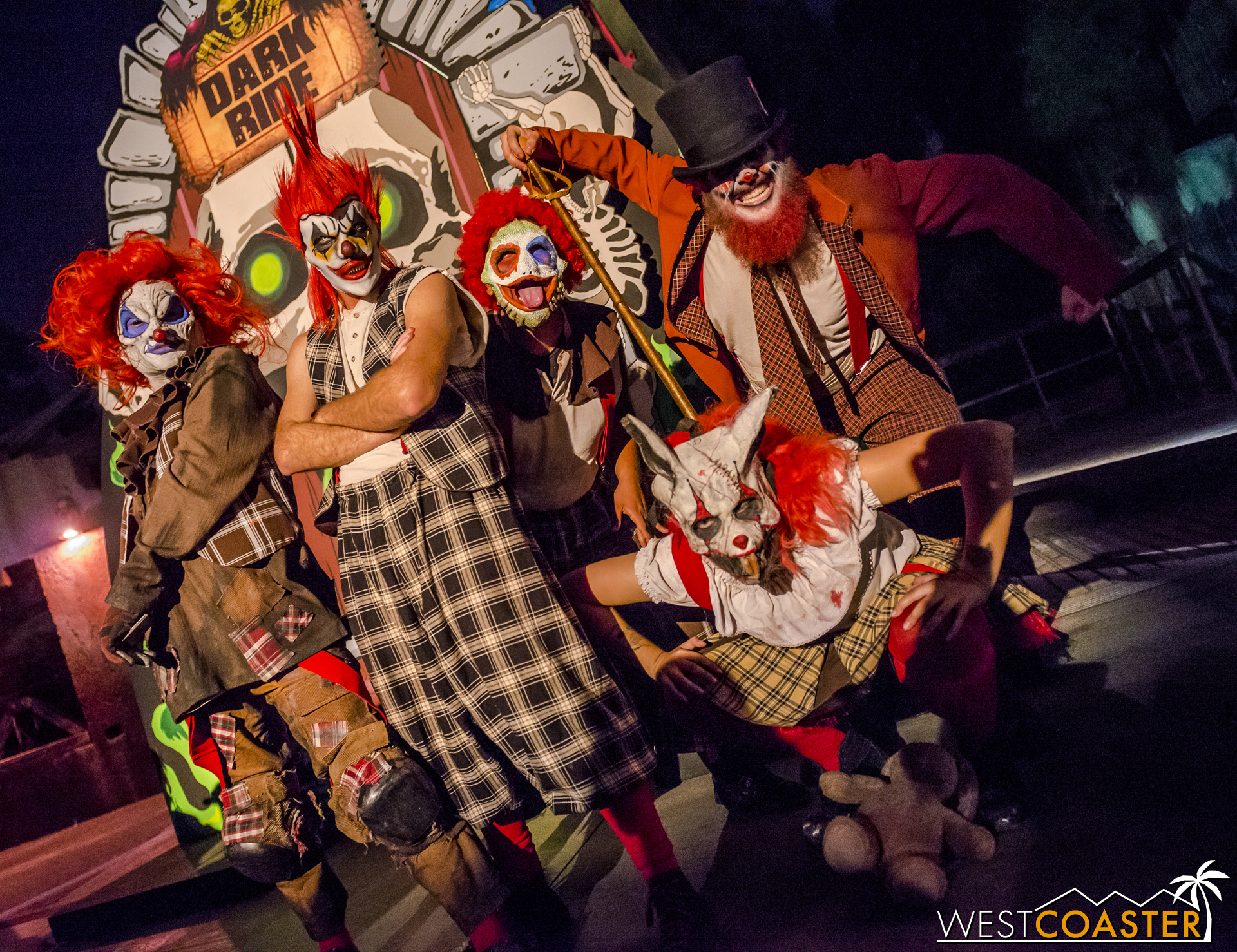 A gang of Carnevil clowns poses in front of the Dark Ride photo op backdrop.