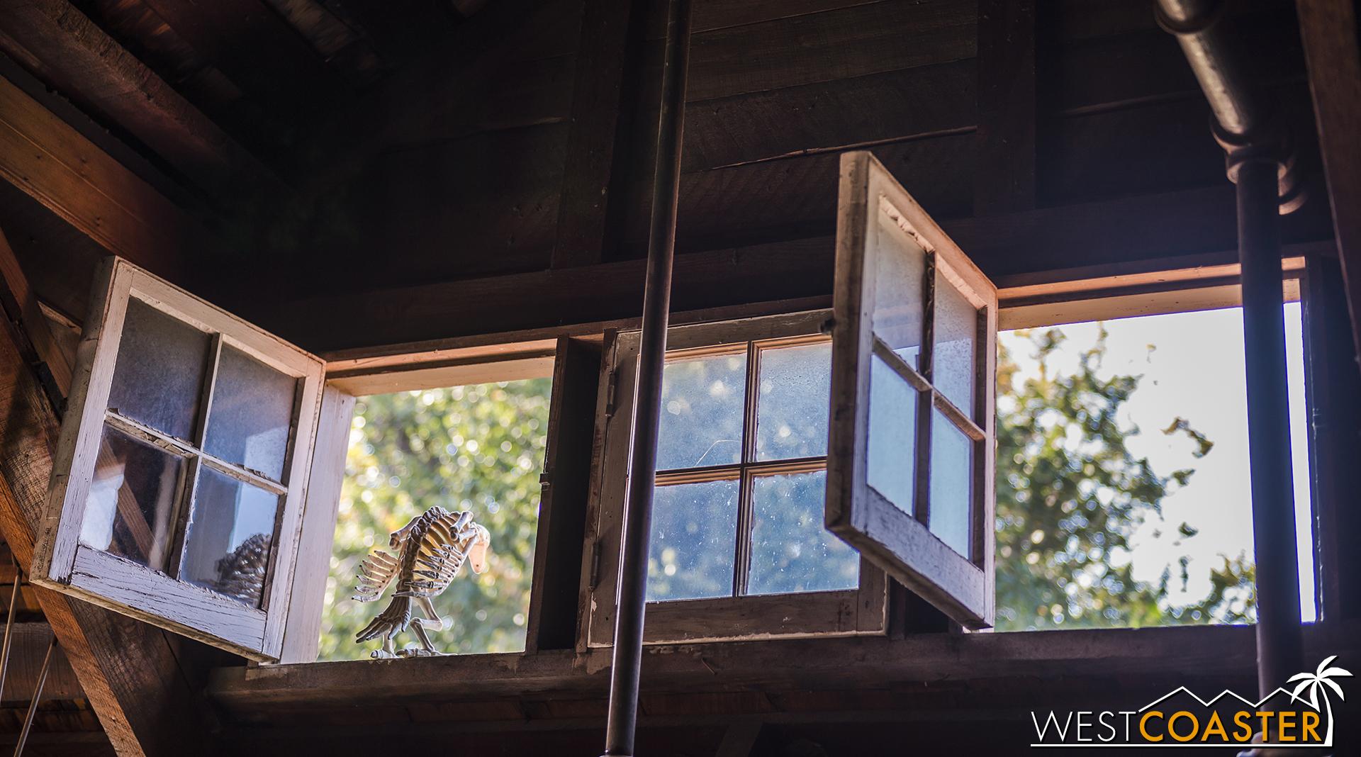 A skeletal bird perches on an open window in the loft.