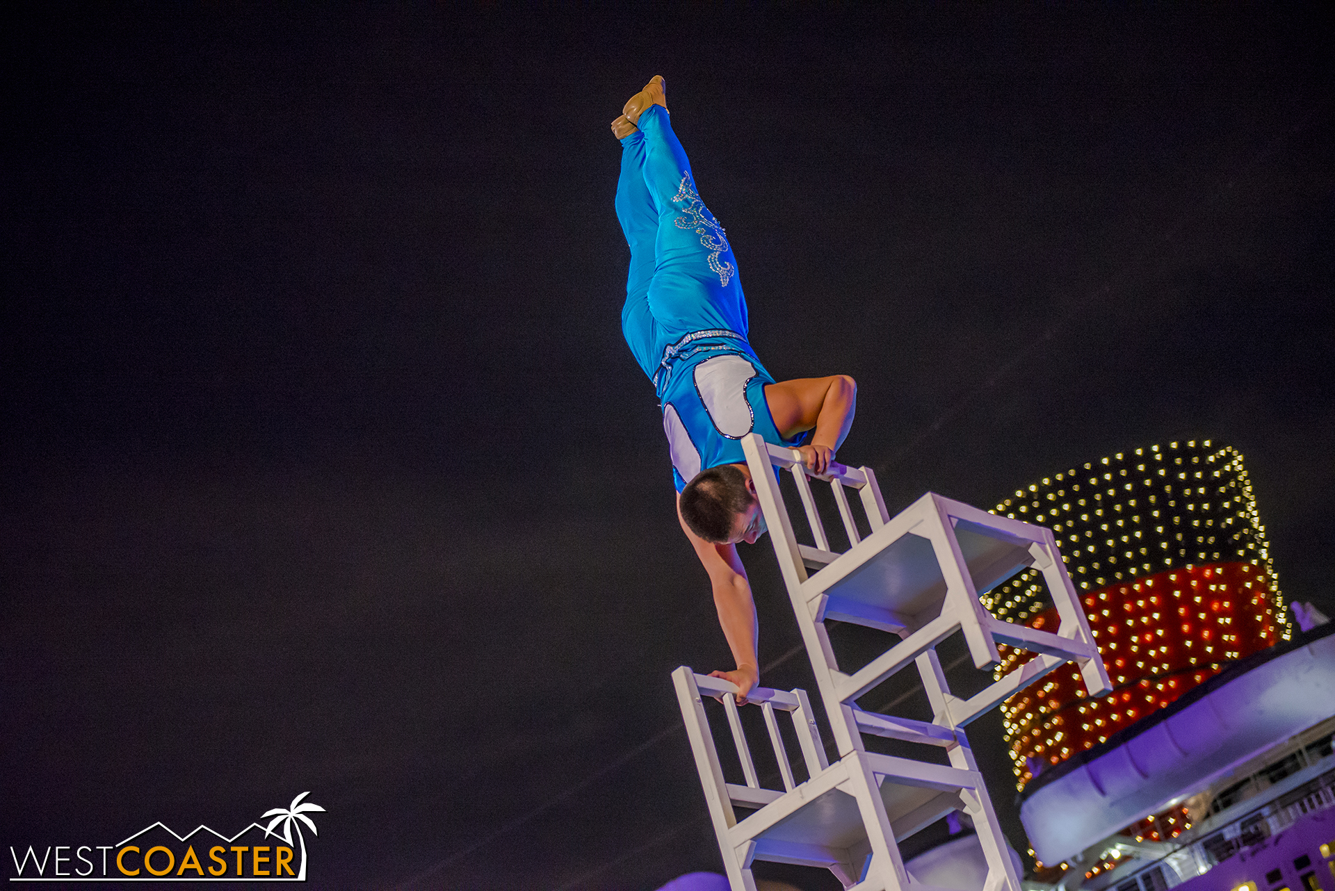 The performer stacks chairs higher and higher to show off his balancing and gymnastic skills.