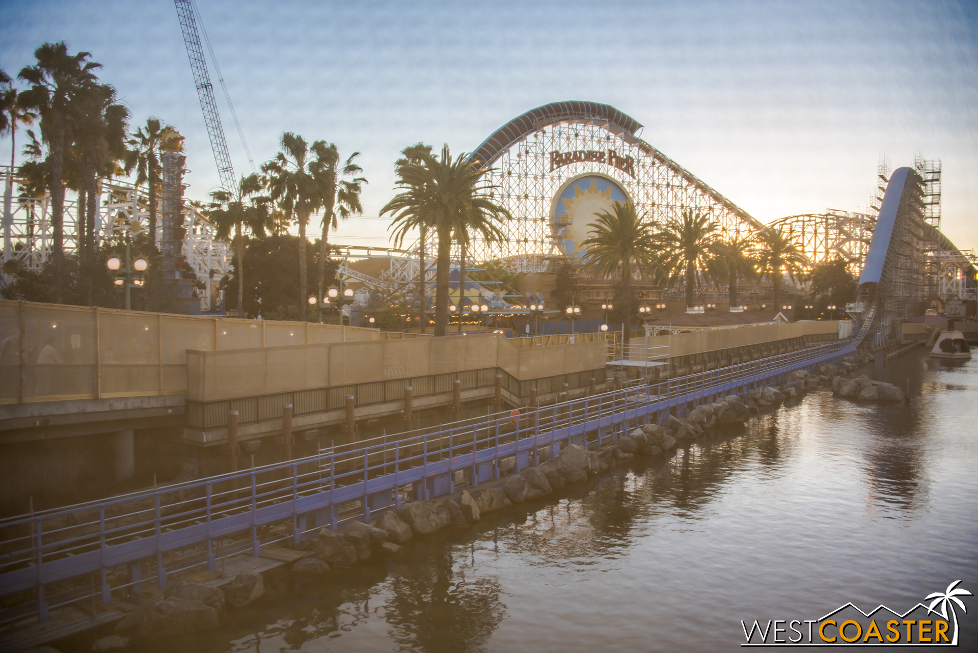 Through the scrim, one can see work happening at Screamin'.