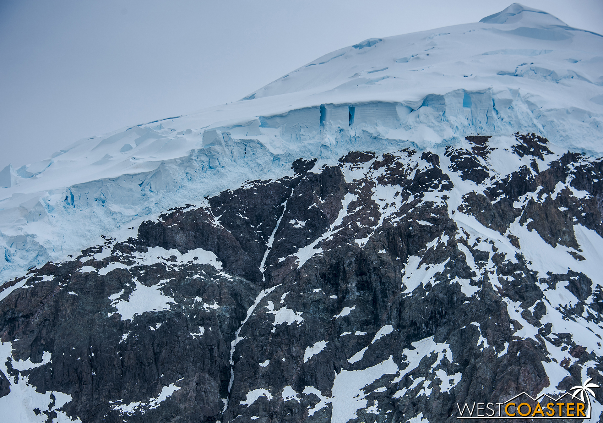 A snowy peak, heavily packed in a deep layer of ice, dramatically textured.
