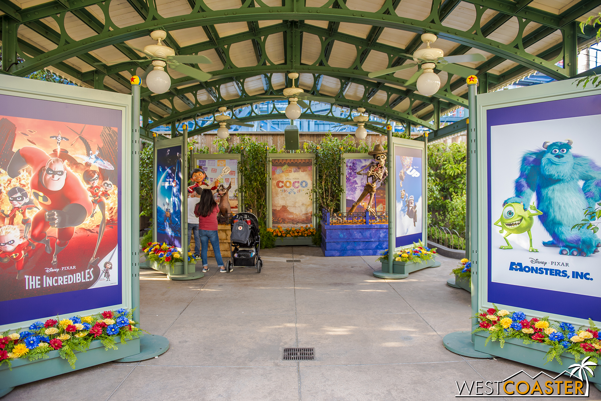 Immediately to the right, where the food festival beer gardens are typically located, is a photo op area with Pixar movie posters and a  Coco  set.