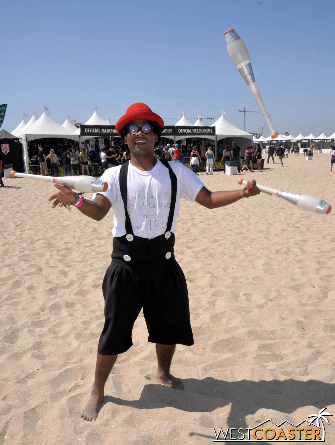 A juggler on hand on the sand.