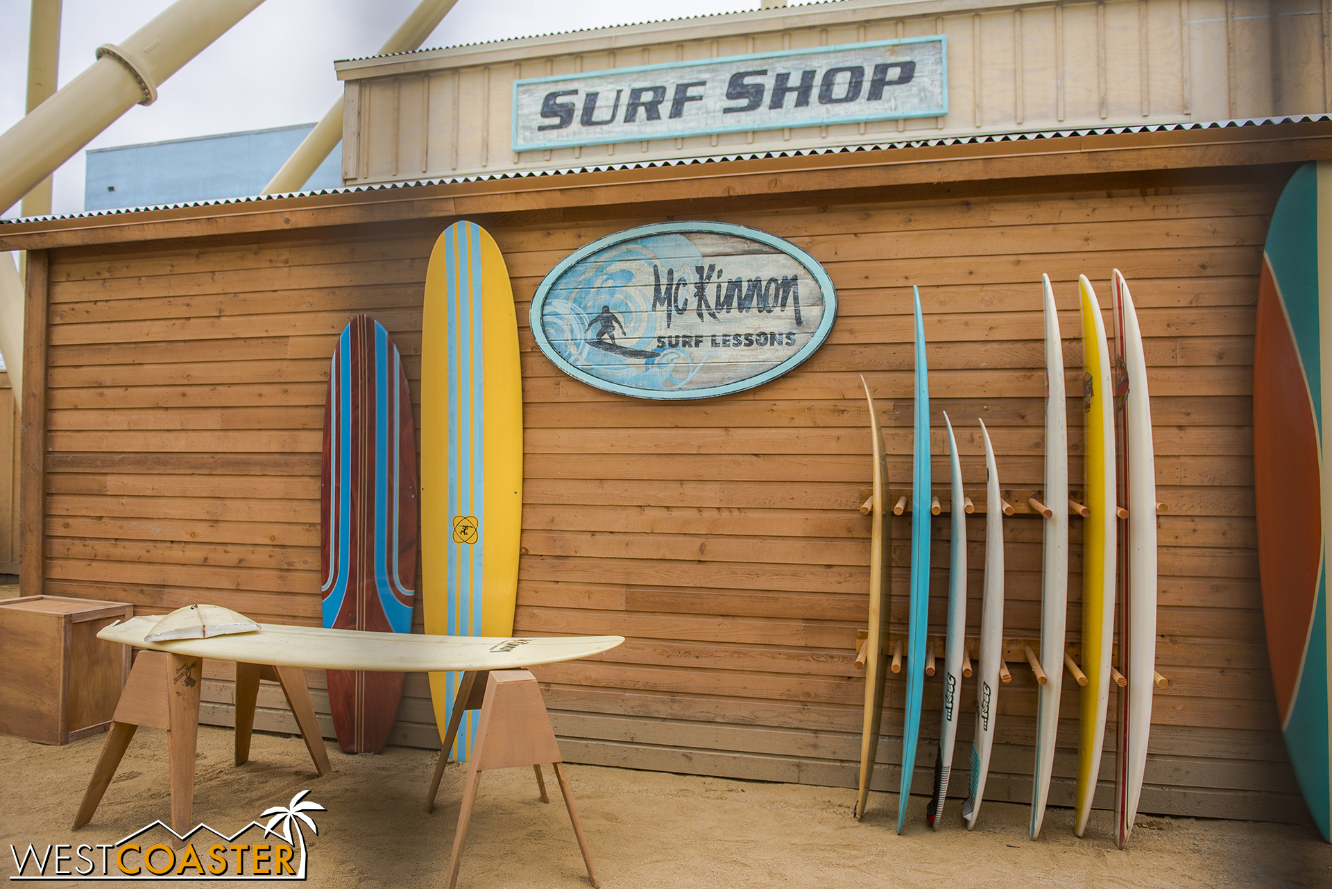 """Lets look at the theming.  There's a """"surf shop"""" behind fencing, visible from the line."""
