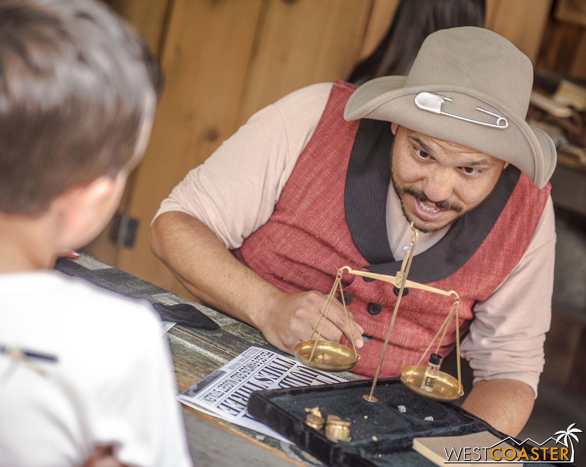 """""""Peg Leg"""" Cinch ascertains the value of gold that a young guest has brought to be assayed."""