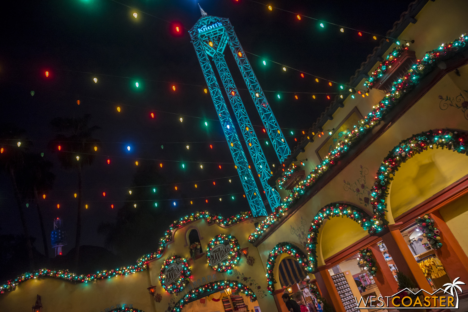 Pretty string lights and lit-up garland accent the buildings over by the Fiesta fountain and arcade.