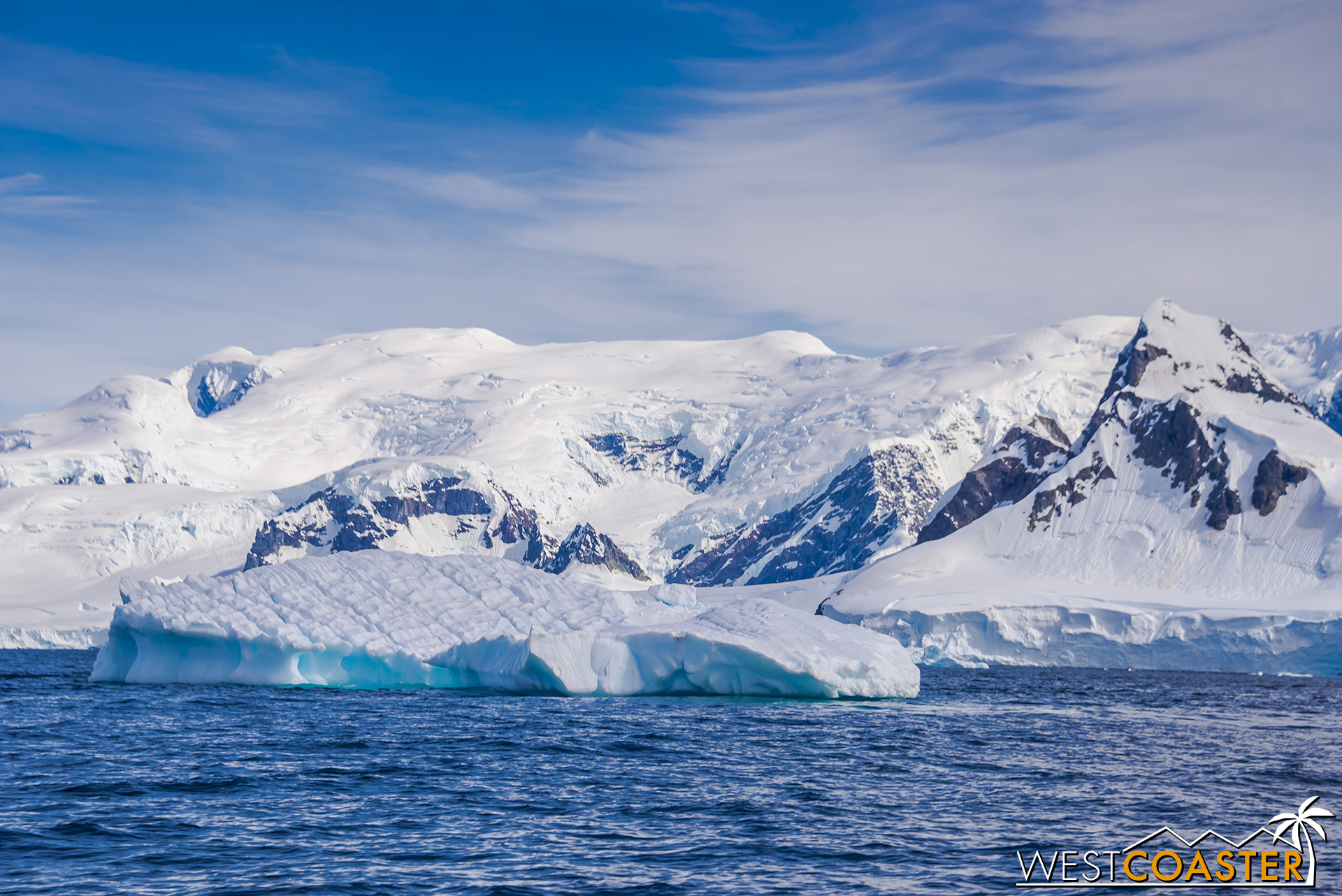 Snowcapped mountains and glaciers from a backdrop in front of large icebergs that are nonetheless dwarfed by their surroundings.