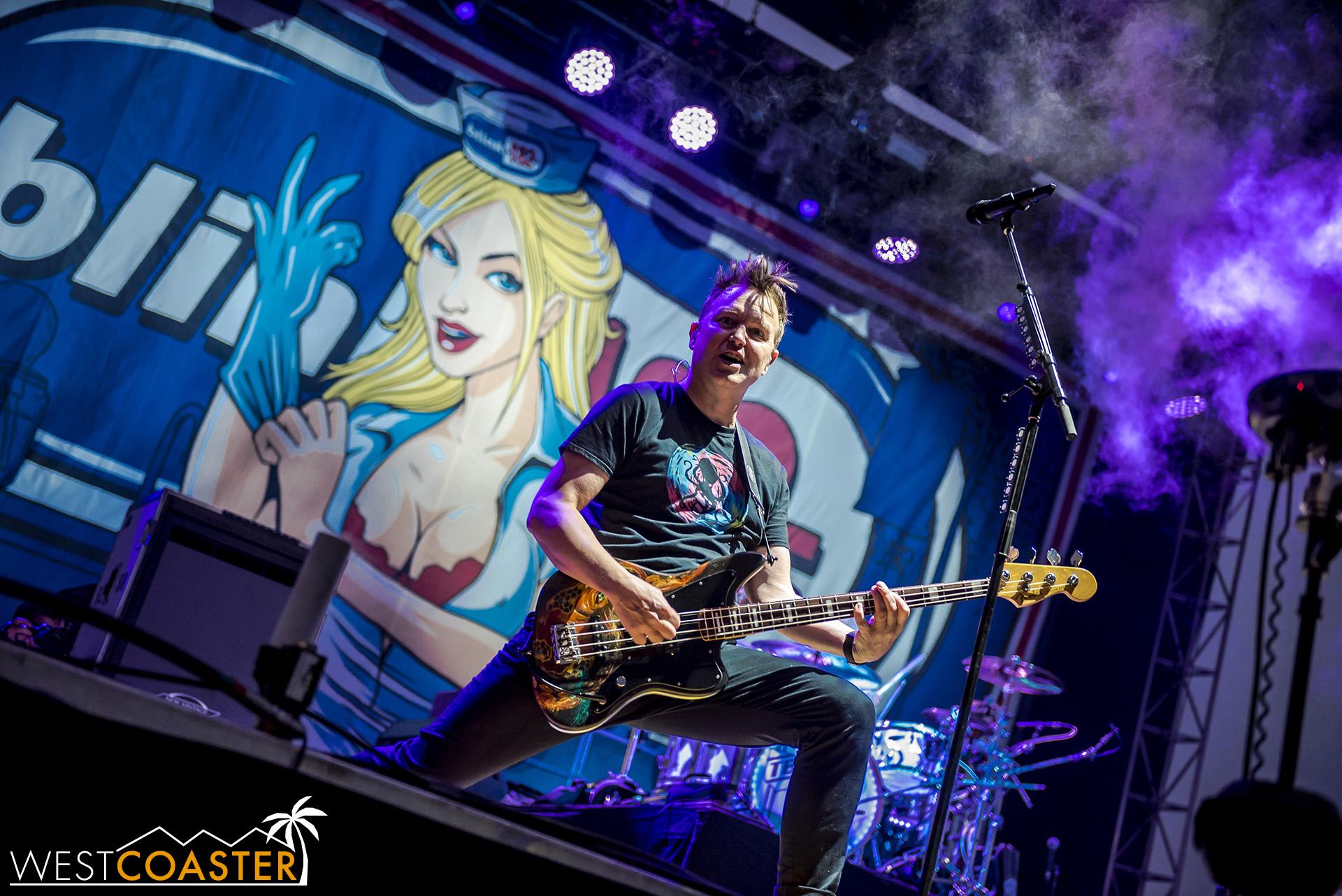 Mark Hoppus striking a power pose on guitar.