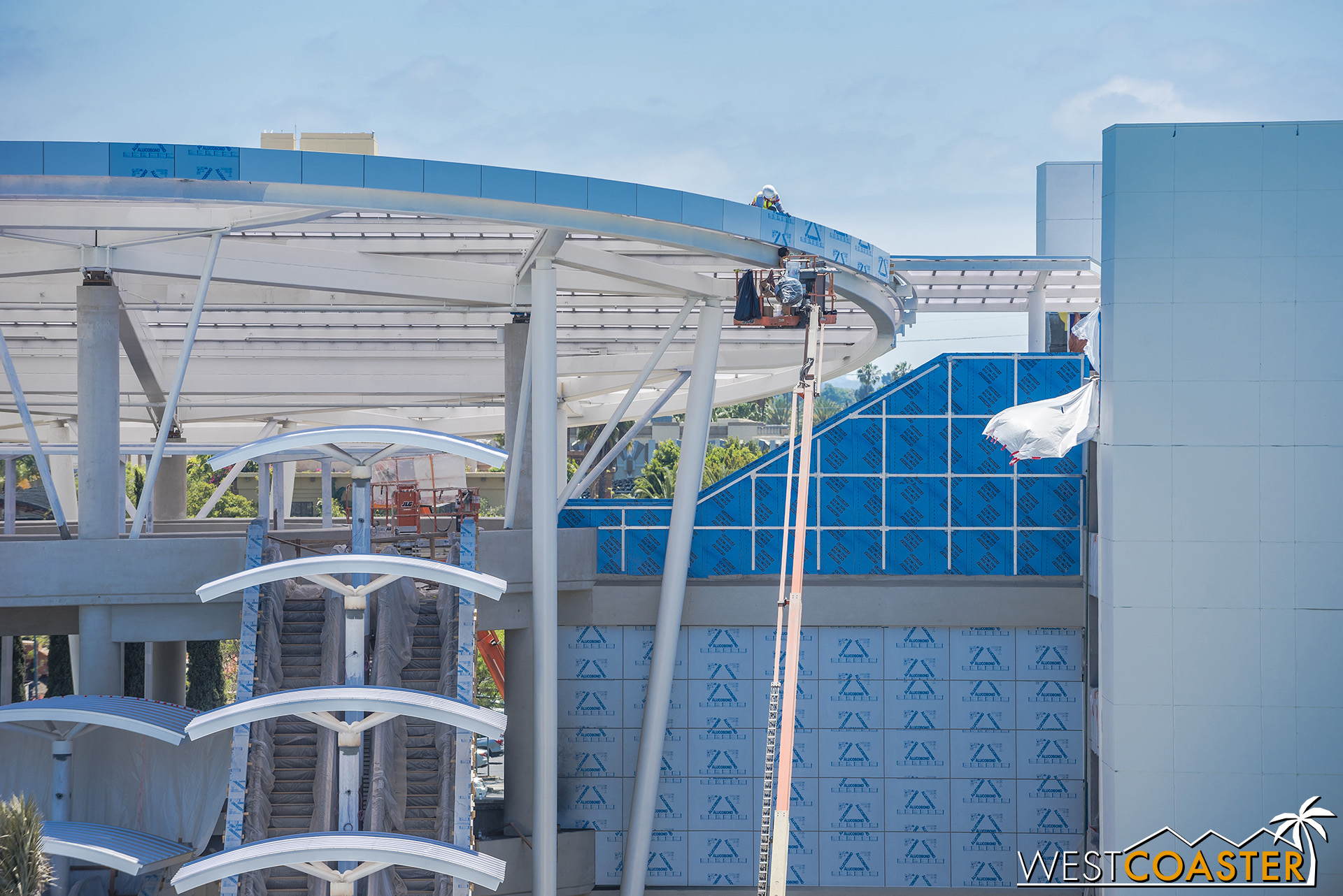 Workers continue to install the aluminum composite panel fascia at the canopy.